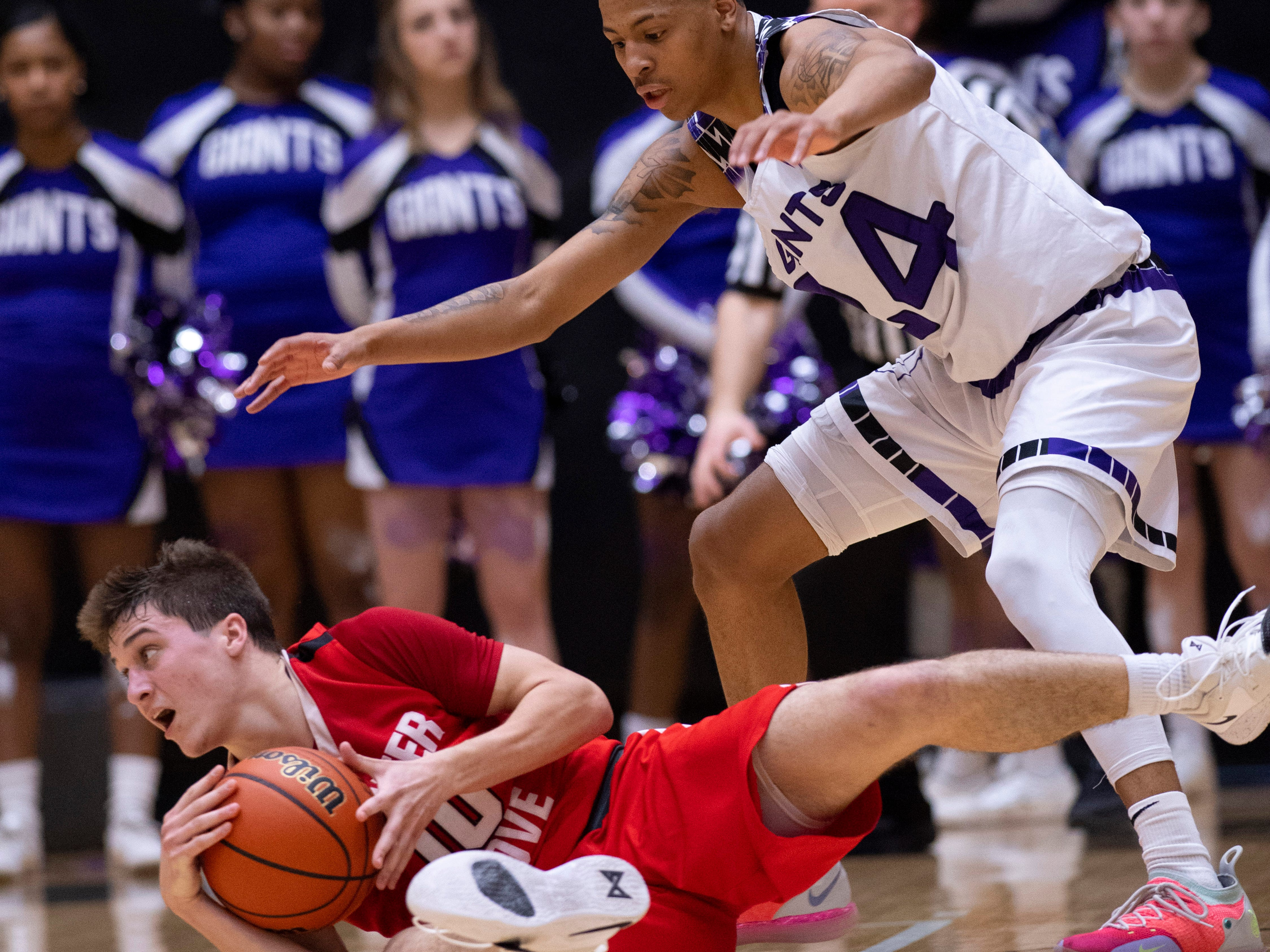 Center Grove's Spencer Piercefield (10) looks for a teammate to pass to while being defended by Ben Davis's Jalen Windham (24) during the 4A Boys Indiana Semi-State Basketball Tournament at the Hatchet House in Washington, Ind., Saturday afternoon.