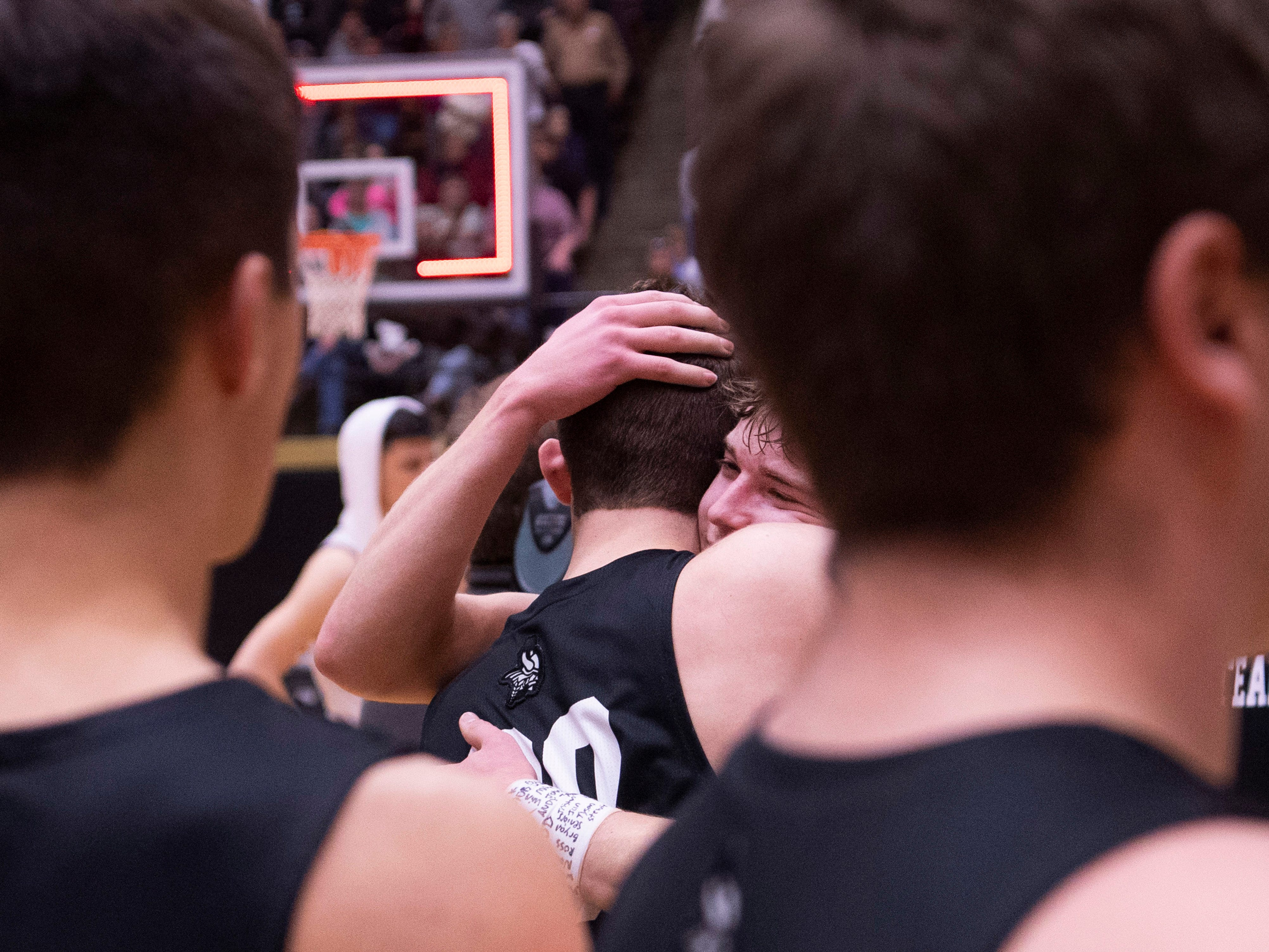 Barr-Reeve's Devin Graber (30) is hugged by Barr-Reeve's Isaac Wagler (12), right center, after the 1A Boys Indiana Semi-State Basketball Tournament at the Hatchet House in Washington, Ind., Saturday afternoon. Barr-Reeve beat Bloomfield to advance to state.