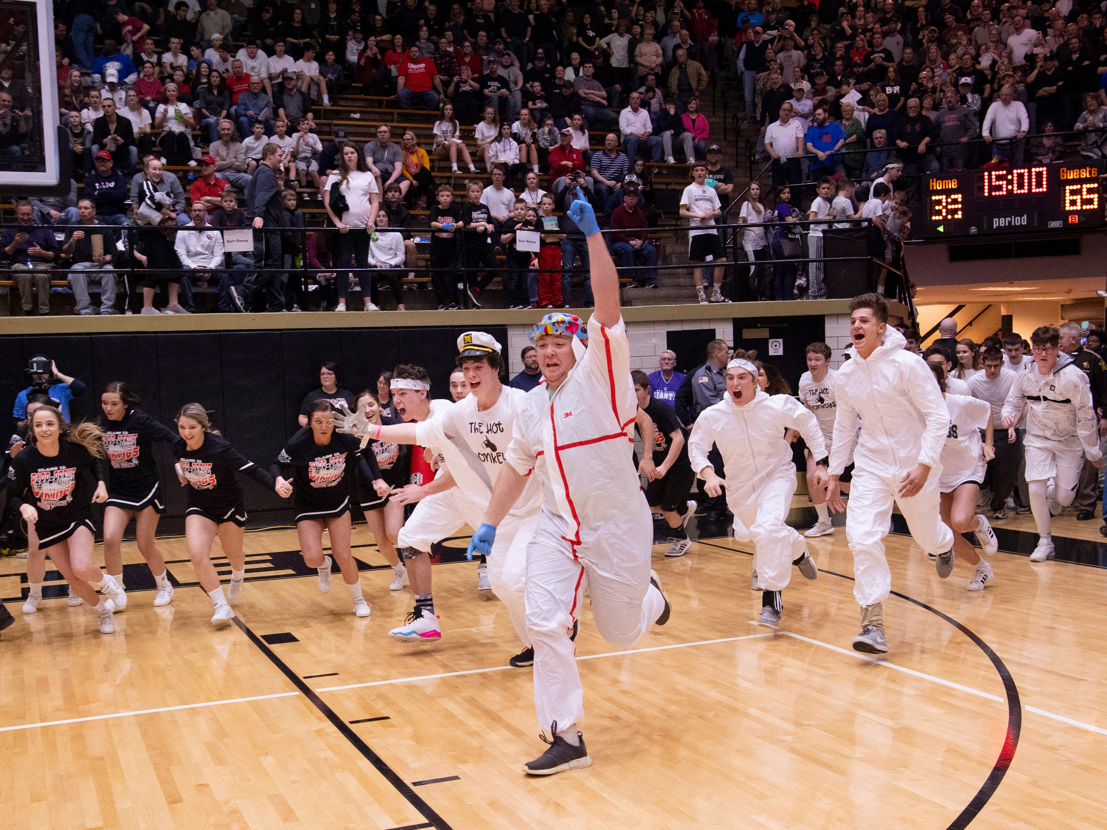 The Barr-Reeve student section storms the court after their team beat Bloomfield in the 1A Boys Indiana Semi-State Basketball Tournament at the Hatchet House in Washington, Ind., Saturday afternoon.