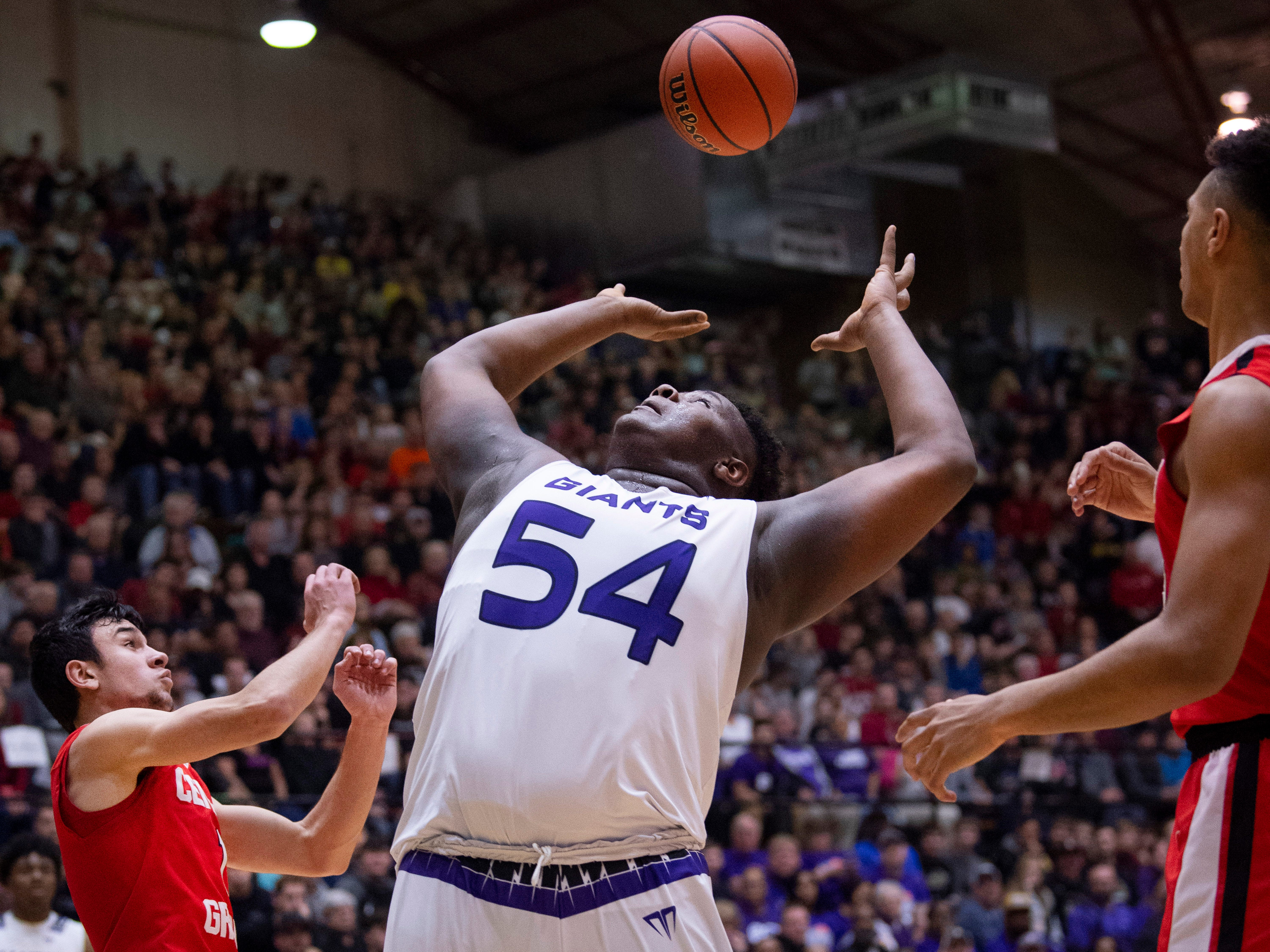 Ben Davis's Dawand Jones (54) grabs a rebound in front of Center Grove's Ben Nicoson (1) and Trayce Jackson-Davis (23) during the 4A Boys Indiana Semi-State Basketball Tournament at the Hatchet House in Washington, Ind., Saturday afternoon.