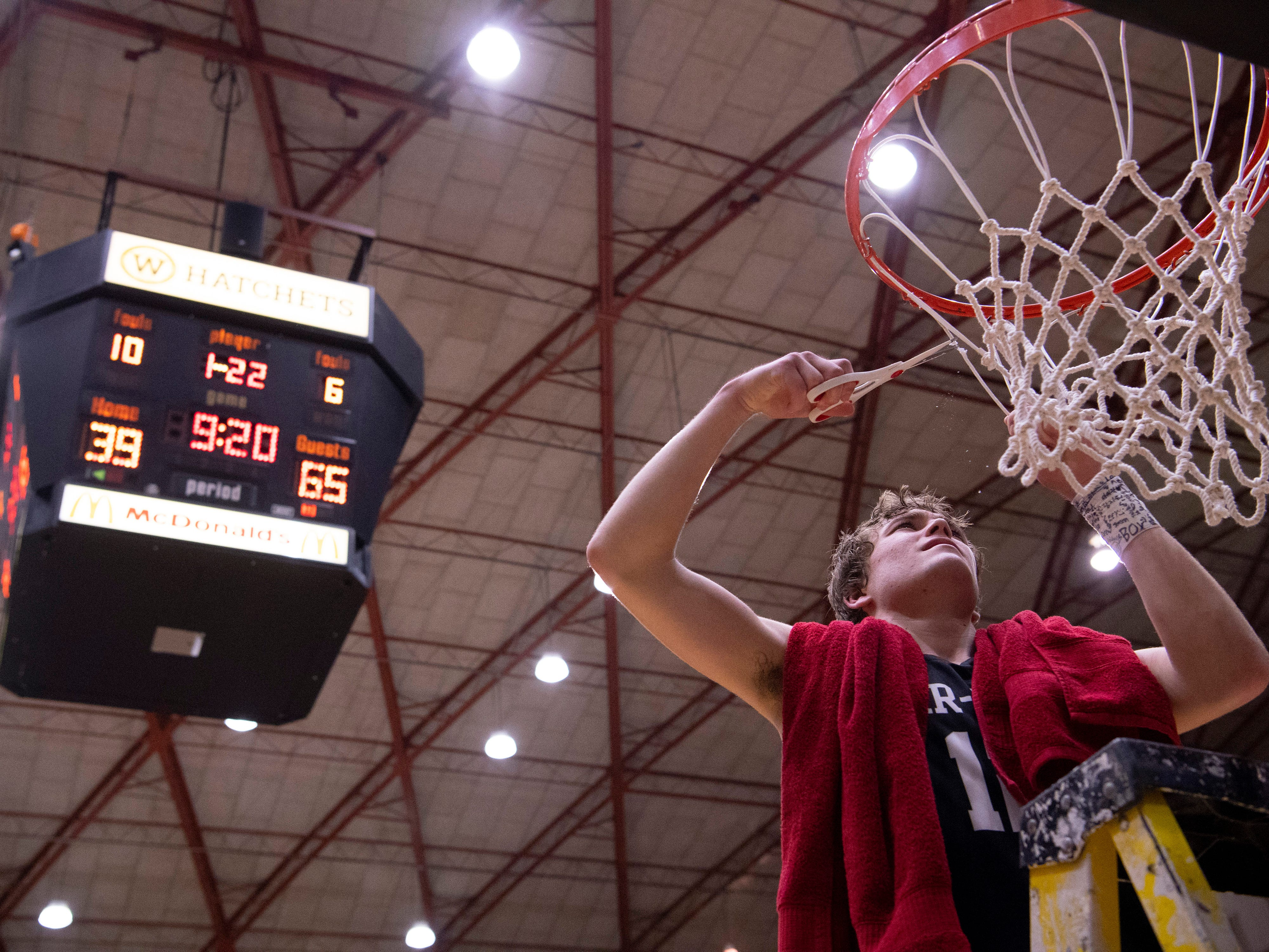 Barr-Reeve's Isaac Wagler (12) cuts down the net after beating Bloomfield in the 1A Boys Indiana Semi-State Basketball Tournament at the Hatchet House in Washington, Ind., Saturday afternoon.