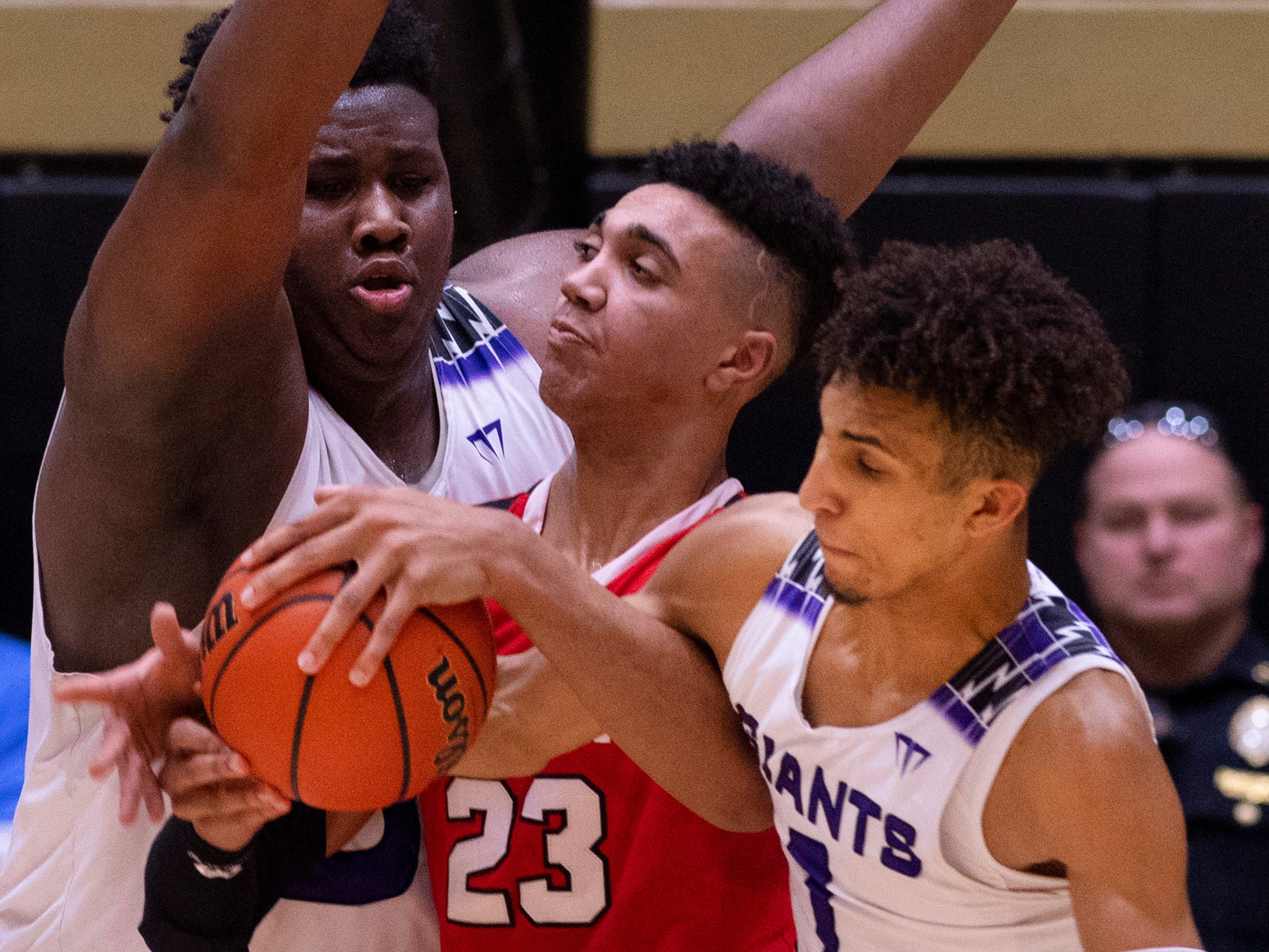 Center Grove's Trayce Jackson-Davis (23) is tangled up with Ben Davis's Dawand Jones (54) and Tyreese Nibbs (1) during the 4A Boys Indiana Semi-State Basketball Tournament at the Hatchet House in Washington, Ind., Saturday afternoon.