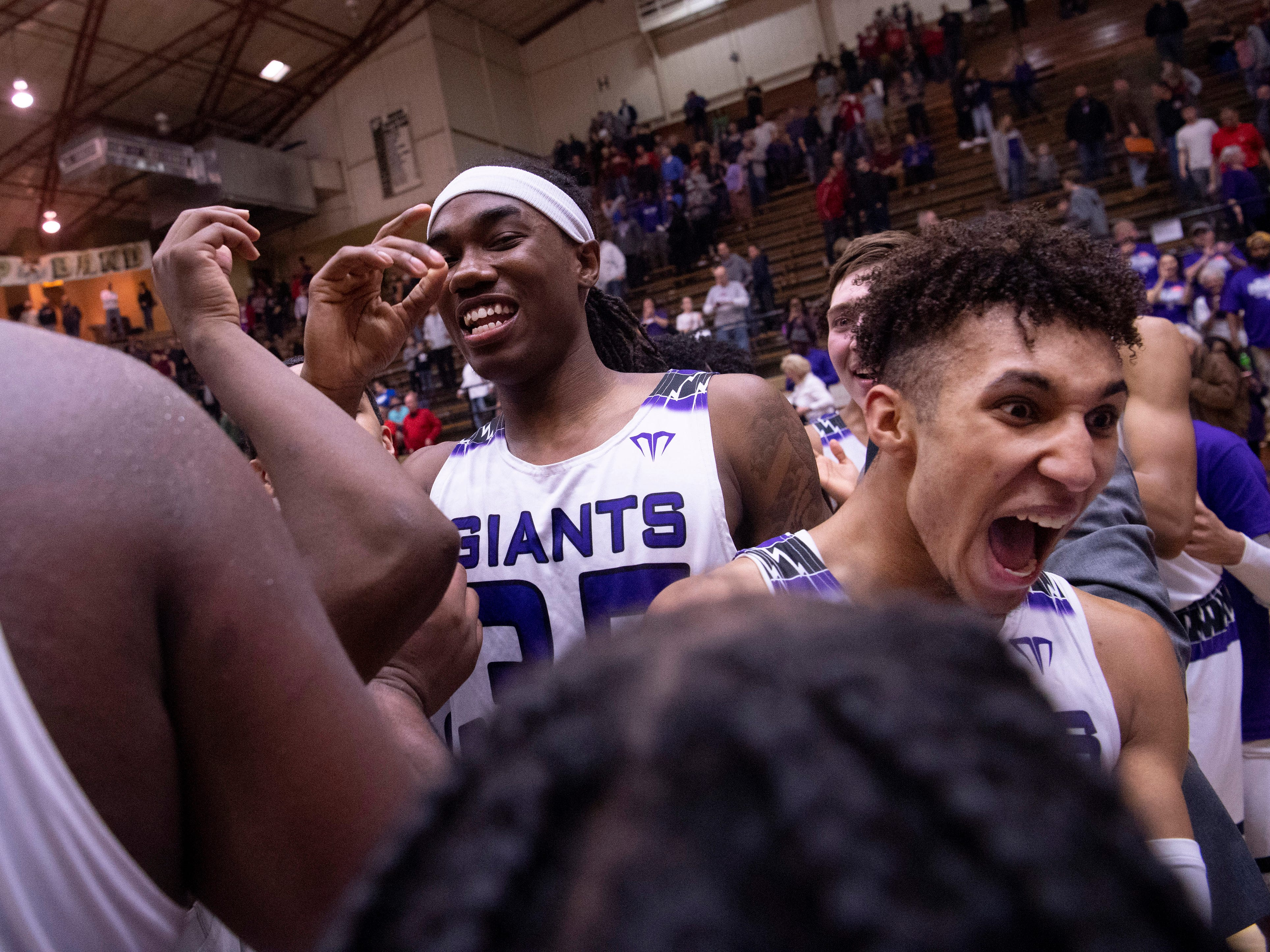 Ben Davis's Jeff Clayton (35), center, celebrates with his team after beating Center Grove in the 4A Boys Indiana Semi-State Basketball Tournament at the Hatchet House in Washington, Ind., Saturday afternoon.