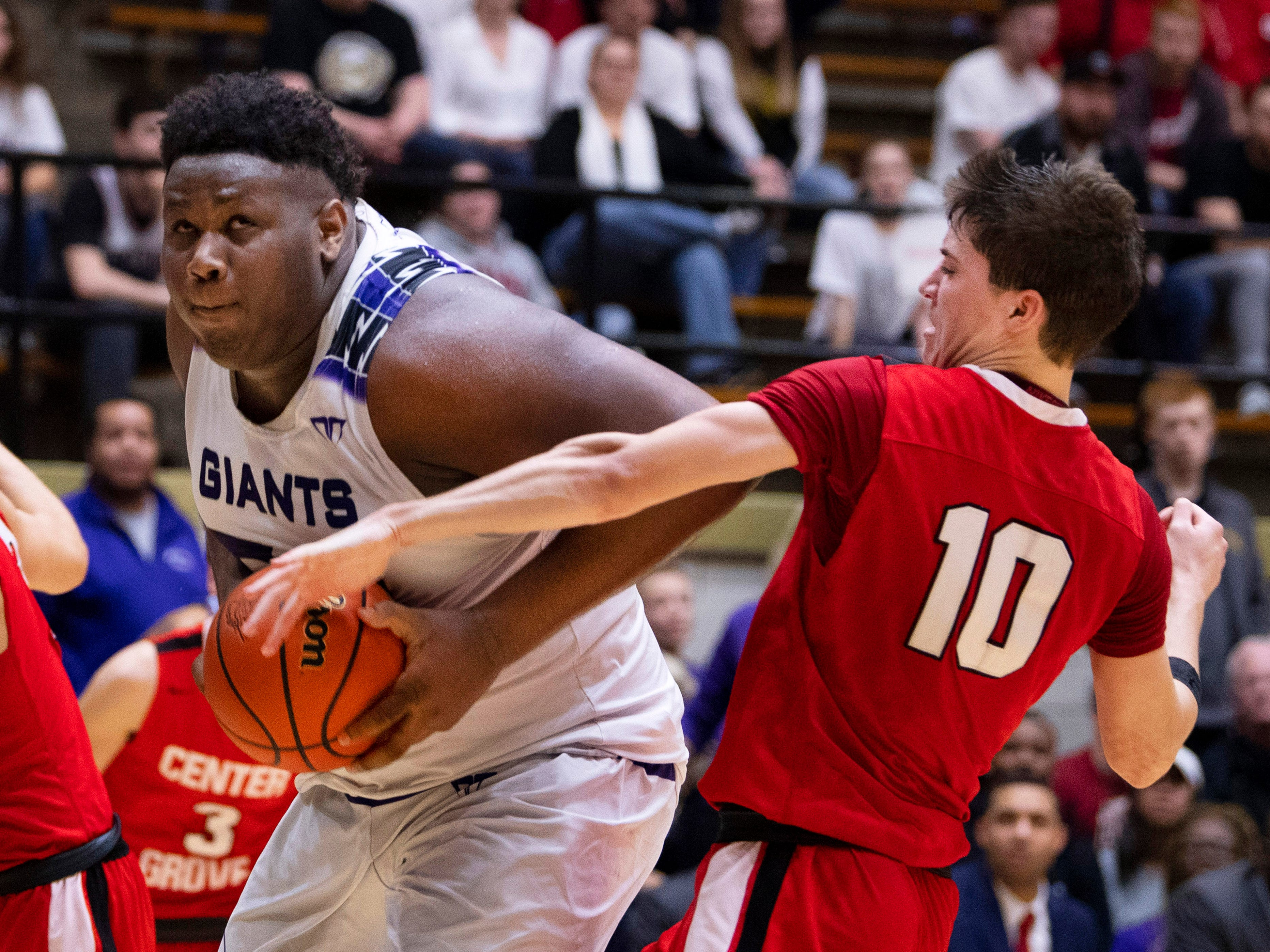 Ben Davis's Dawand Jones (54) powers to the basket for two points while being defended by Center Grove's Spencer Piercefield (10) and Justin DeGraaf (13) during the 4A Boys Indiana Semi-State Basketball Tournament at the Hatchet House in Washington, Ind., Saturday afternoon.
