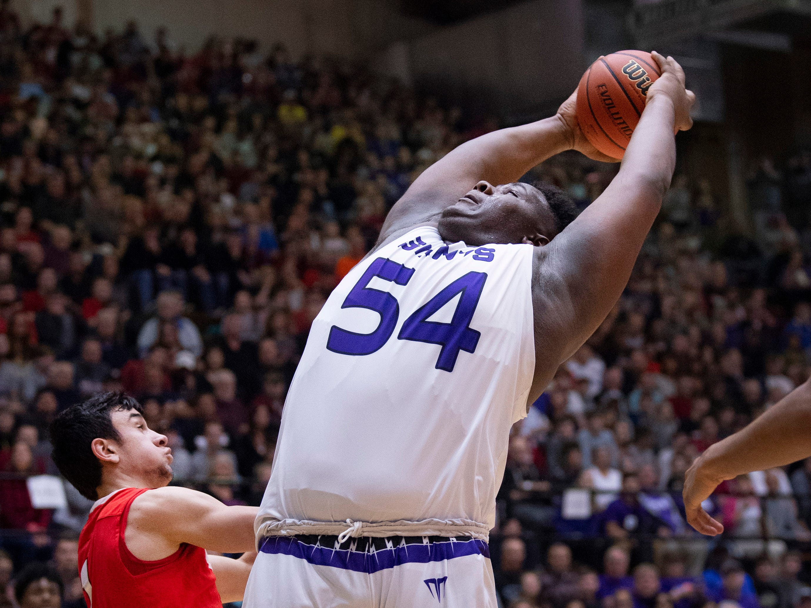 Ben Davis's Dawand Jones (54) grabs a rebound in front of Center Grove's Ben Nicoson (1) during the 4A Boys Indiana Semi-State Basketball Tournament at the Hatchet House in Washington, Ind., Saturday afternoon.
