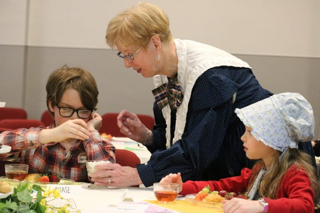 Bette Kaltenbach, a volunteer, offers sugar cubes for the tea to Henry and Fiona McGrew during the Victorian Tea Party at the Hayes Presidential Library & Museums on Saturday.