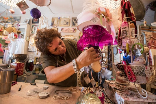 Linda Ashby, owner of The Tainted Lady Brocante & Antiques in Cape Coral, arranges one of her displays Wednesday, February 27, 2019.