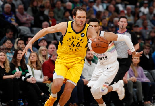 Indiana Pacers forward Bojan Bogdanovic, front, drives past Denver Nuggets guard Jamal Murray during the first half of an NBA basketball game Saturday, March 16, 2019, in Denver. (AP Photo/David Zalubowski)