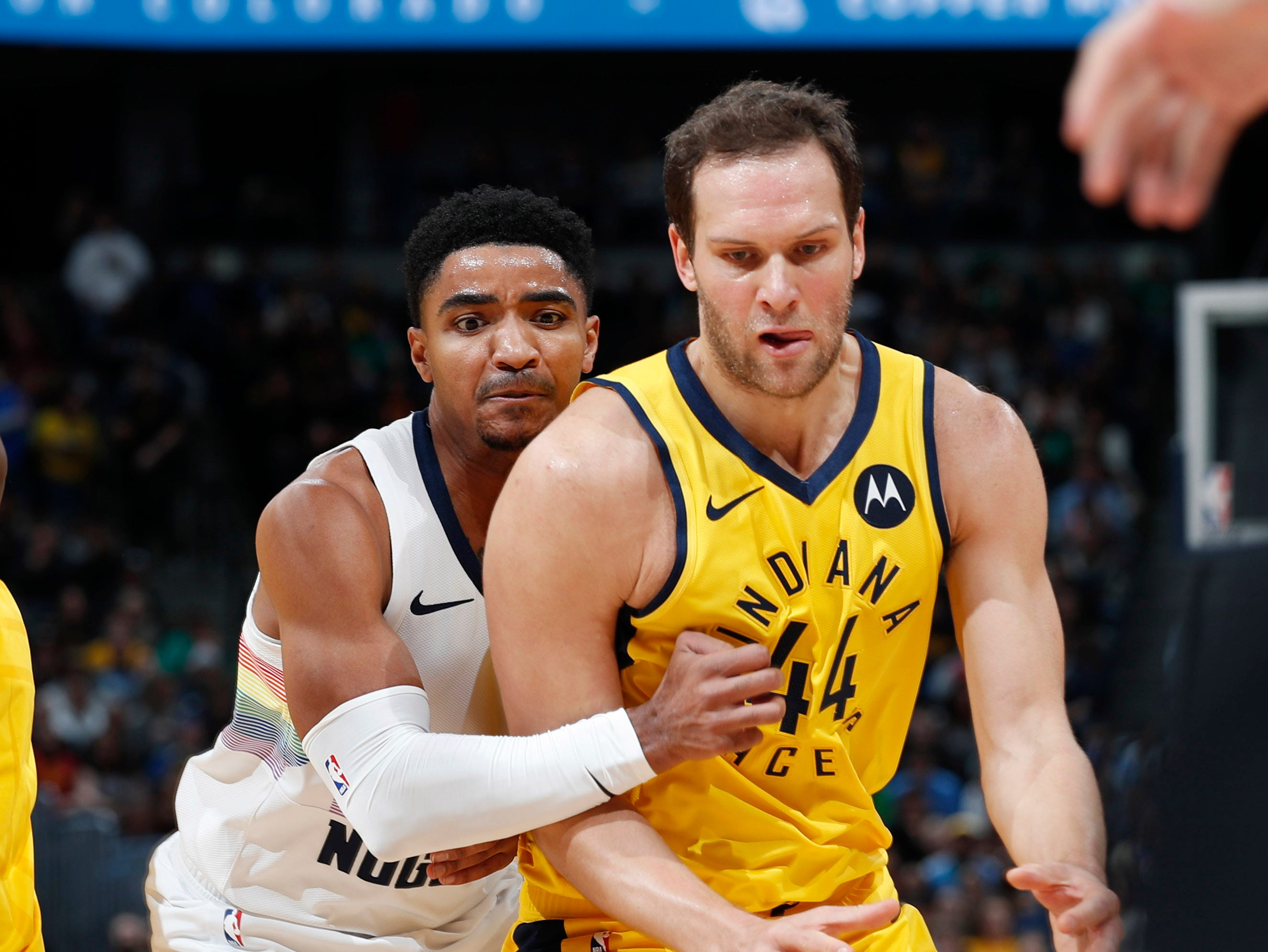 Indiana Pacers forward Bojan Bogdanovic, front, and Denver Nuggets guard Gary Harris watch the ball get away during the first half of an NBA basketball game Saturday, March 16, 2019, in Denver. (AP Photo/David Zalubowski)