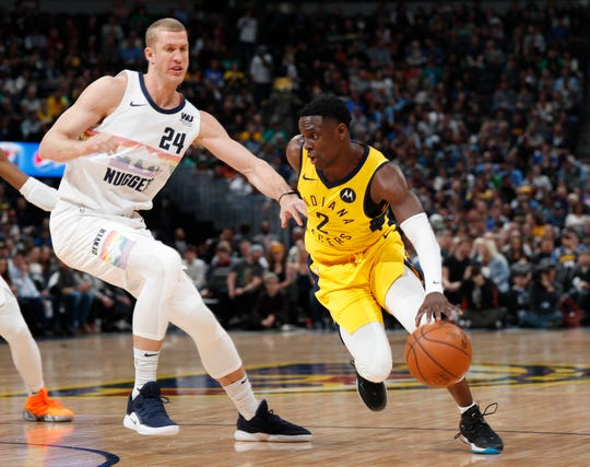 Indiana Pacers guard Darren Collison, right, drives the lane past Denver Nuggets forward Mason Plumlee during the first half of an NBA basketball game Saturday, March 16, 2019, in Denver. (AP Photo/David Zalubowski)