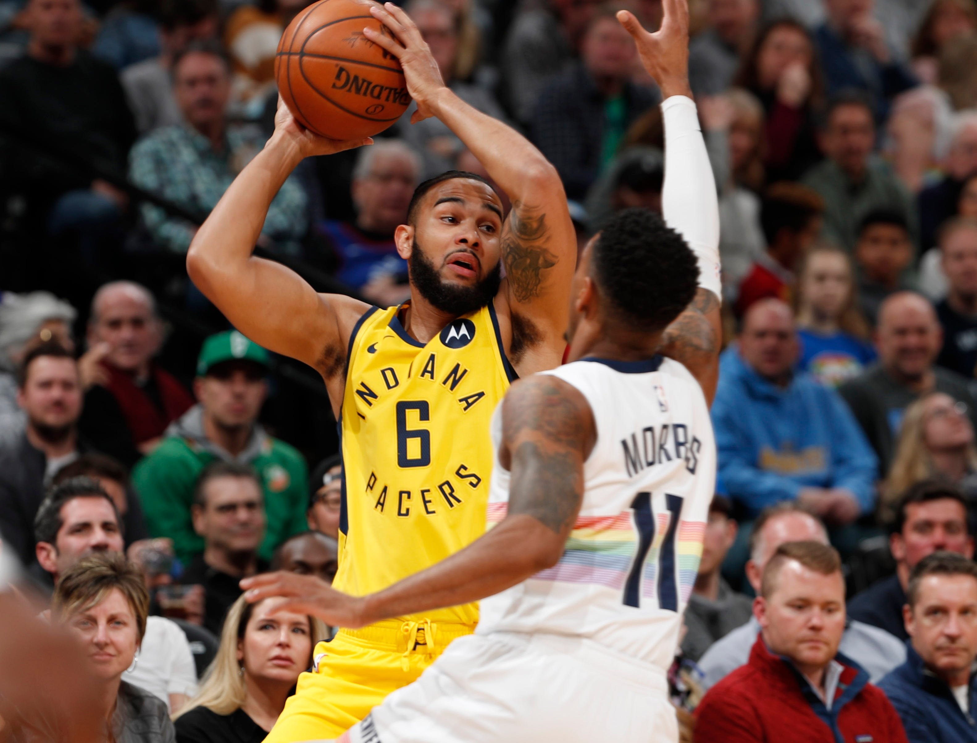 Indiana Pacers guard Cory Joseph, back, looks to pass the ball under pressure from Denver Nuggets guard Monte Morris during the first half of an NBA basketball game Saturday, March 16, 2019, in Denver. (AP Photo/David Zalubowski)