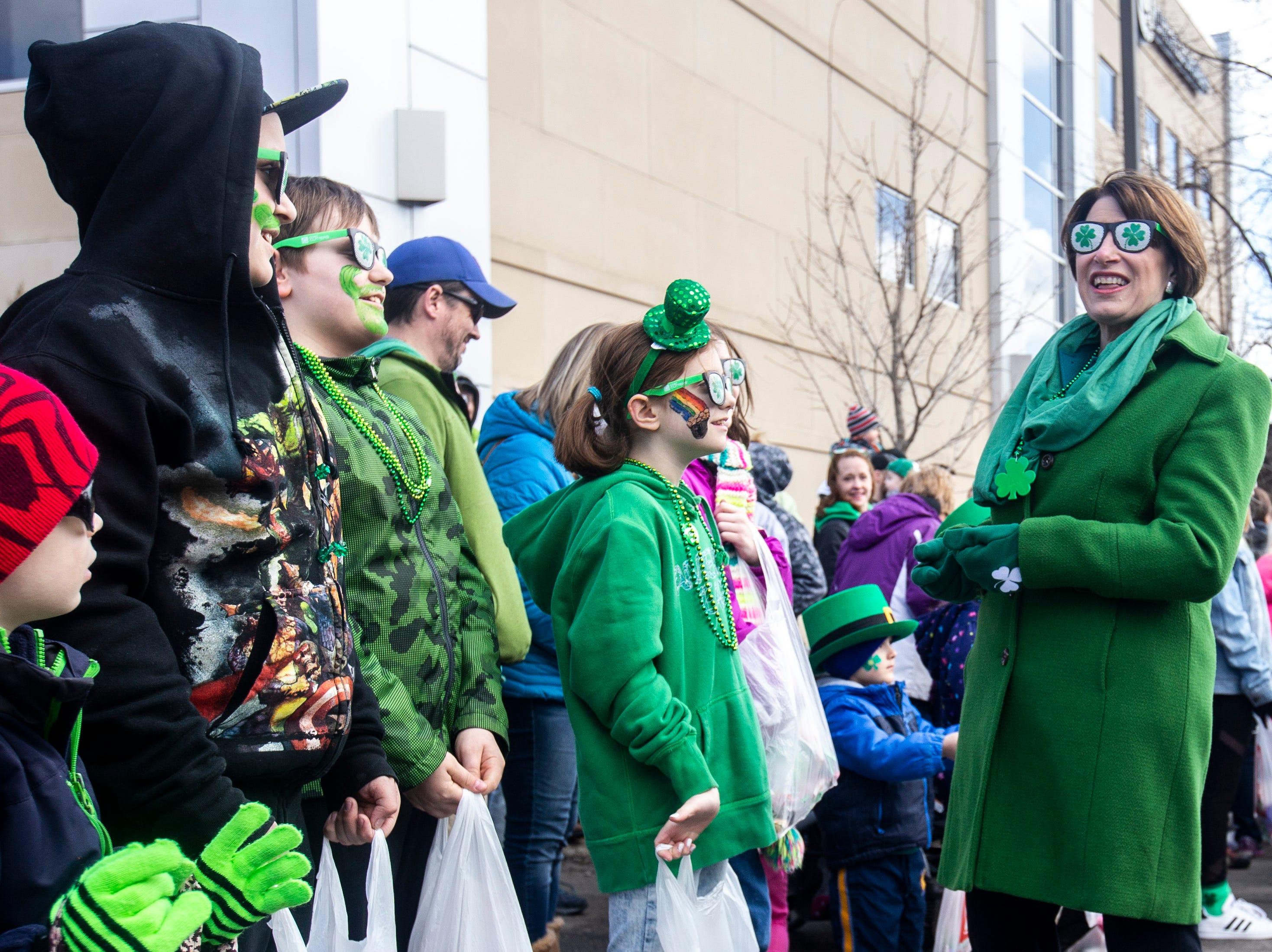 U.S. Sen. Amy Klobuchar, D-Minn., tries on a pair of shamrock sunglasses while walking in the Saint Patrick's Day Parade Society (SaPaDaPaSo) parade on Sunday, March 17, 2019, in downtown Cedar Rapids, Iowa.