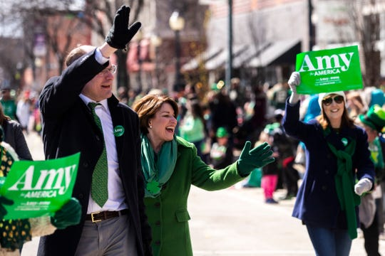 U.S. Sen. Amy Klobuchar, D-Minn., waves to people while walking with her husband John Bessler, left, in the Saint Patrick's Day Parade Society (SaPaDaPaSo) parade on Sunday, March 17, 2019, in downtown Cedar Rapids, Iowa.