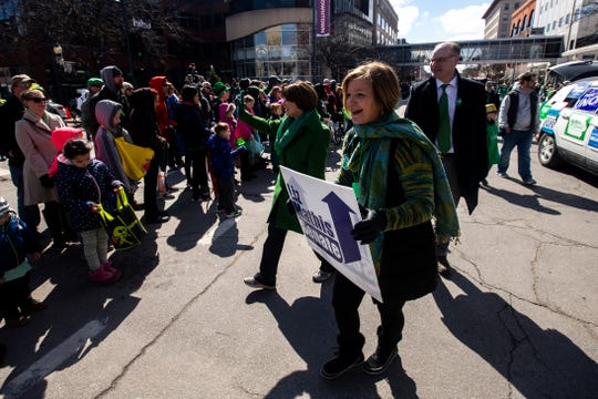 U.S. Sen. Amy Klobuchar, D-Minn., waves to people while walking with her husband John Bessler and Iowa Sen. Liz Mathis, D-Hiawatha, in the Saint Patrick's Day Parade Society (SaPaDaPaSo) parade on Sunday, March 17, 2019, in downtown Cedar Rapids, Iowa.