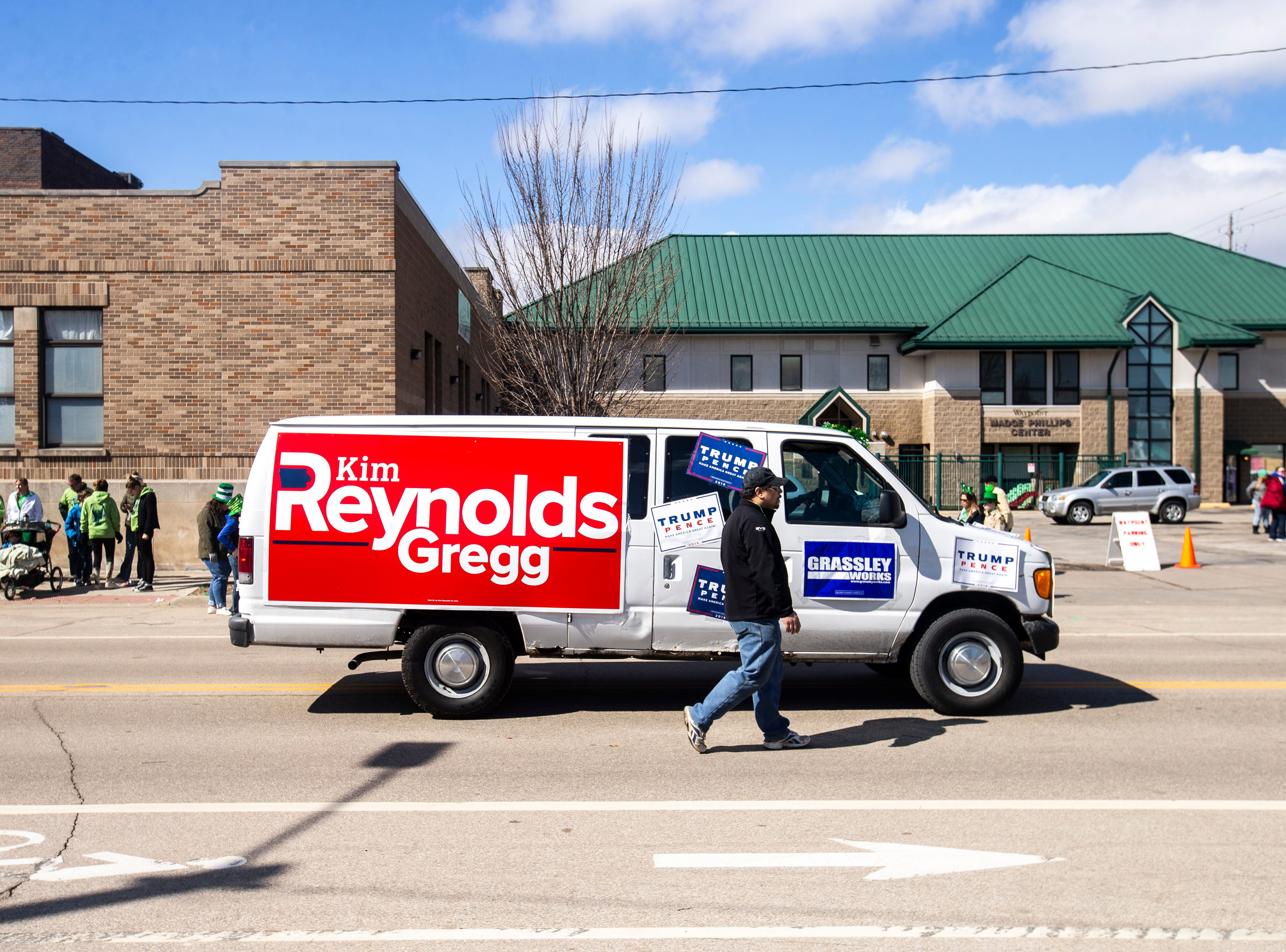 A white panel van decorated with signs for Iowa Governor Kim Reynolds, Donald Trump/Mike Pence and Chuck Grassley drives in the Saint Patrick's Day Parade Society (SaPaDaPaSo) parade on Sunday, March 17, 2019, in downtown Cedar Rapids, Iowa.