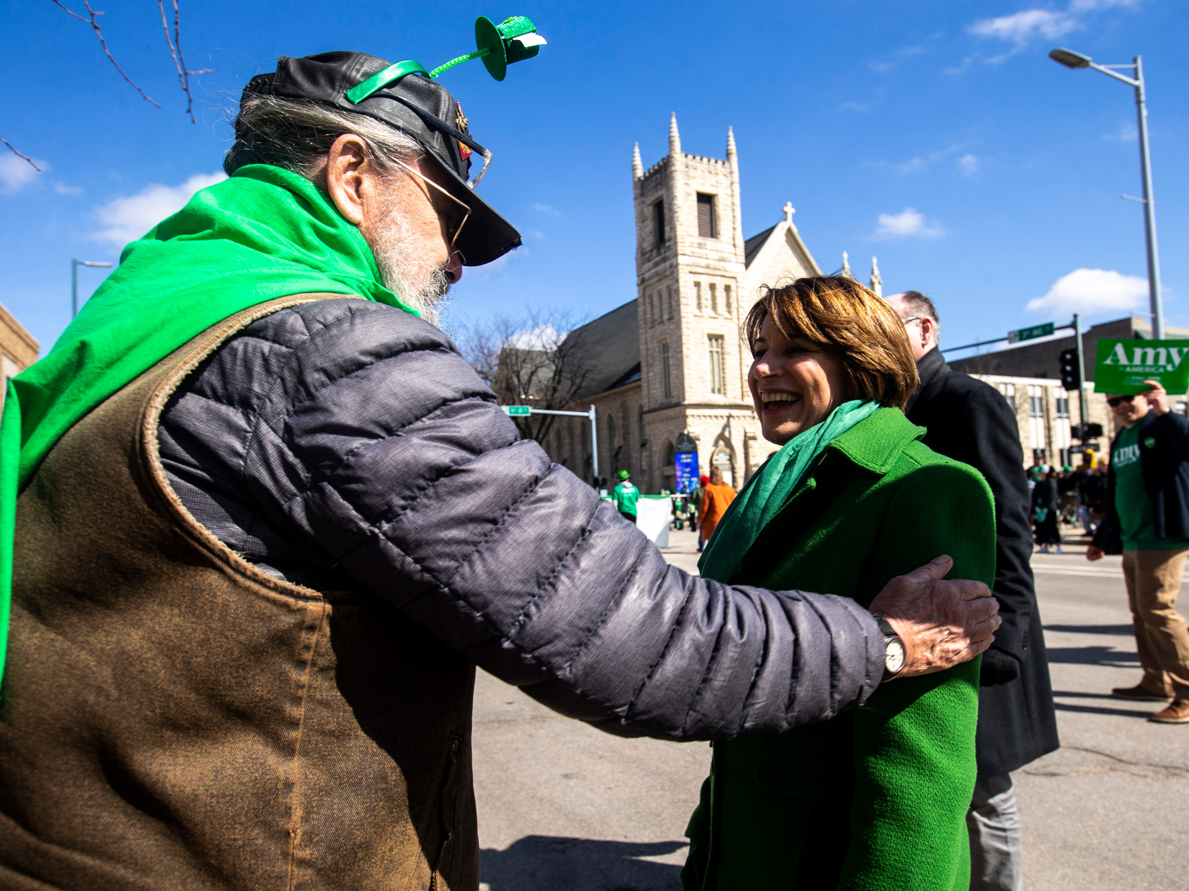 U.S. Sen. Amy Klobuchar, D-Minn., meets with a Cedar Rapids resident who welcomed her to the city while she walked in the Saint Patrick's Day Parade Society (SaPaDaPaSo) parade on Sunday, March 17, 2019, in downtown Cedar Rapids, Iowa.