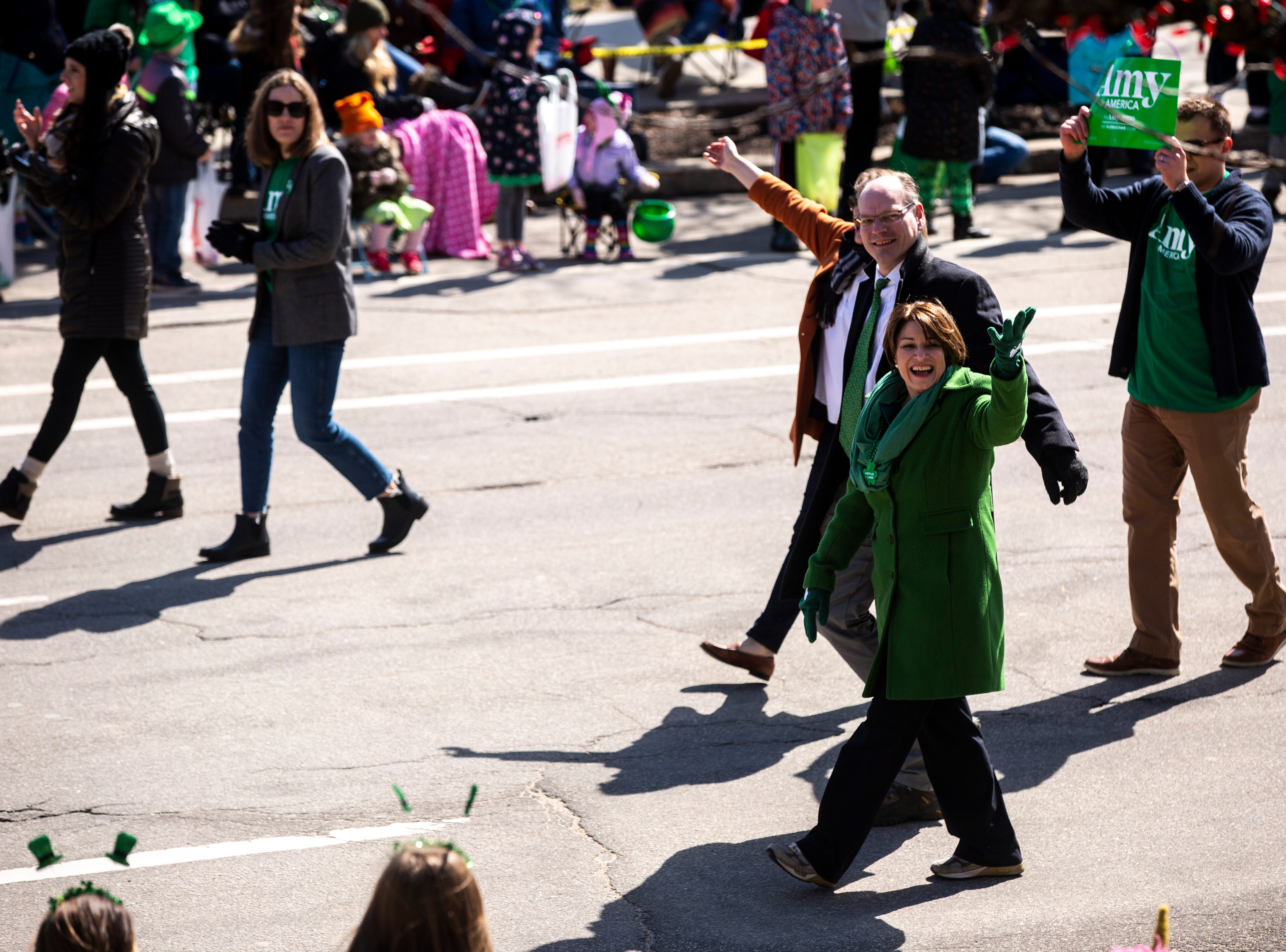 U.S. Sen. Amy Klobuchar, D-Minn., waves to people while walking with her husband John Bessler in the Saint Patrick's Day Parade Society (SaPaDaPaSo) parade on Sunday, March 17, 2019, in downtown Cedar Rapids, Iowa.