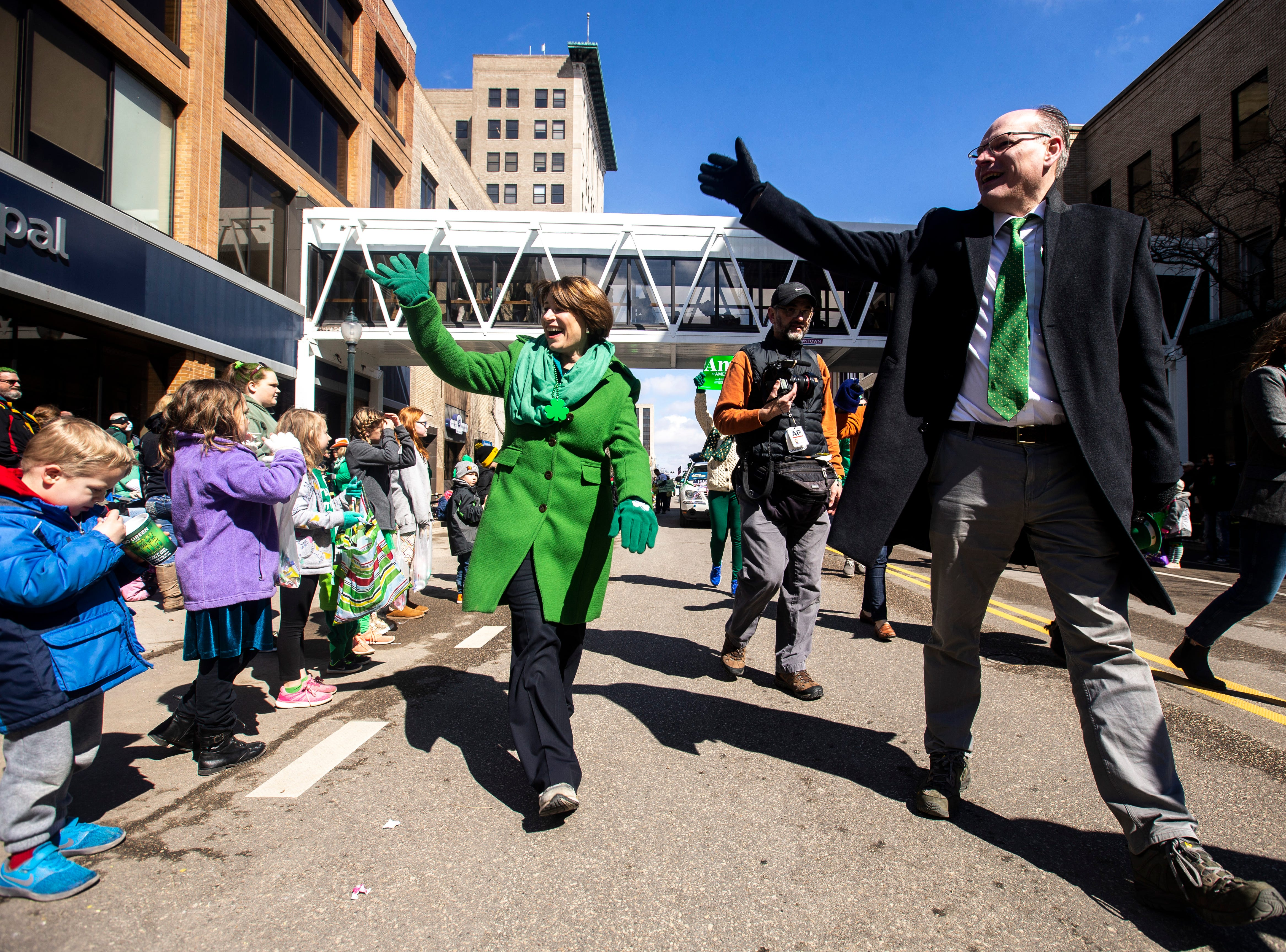 U.S. Sen. Amy Klobuchar, D-Minn., waves to people while walking with her husband John Bessler, right, in the Saint Patrick's Day Parade Society (SaPaDaPaSo) parade on Sunday, March 17, 2019, in downtown Cedar Rapids, Iowa.