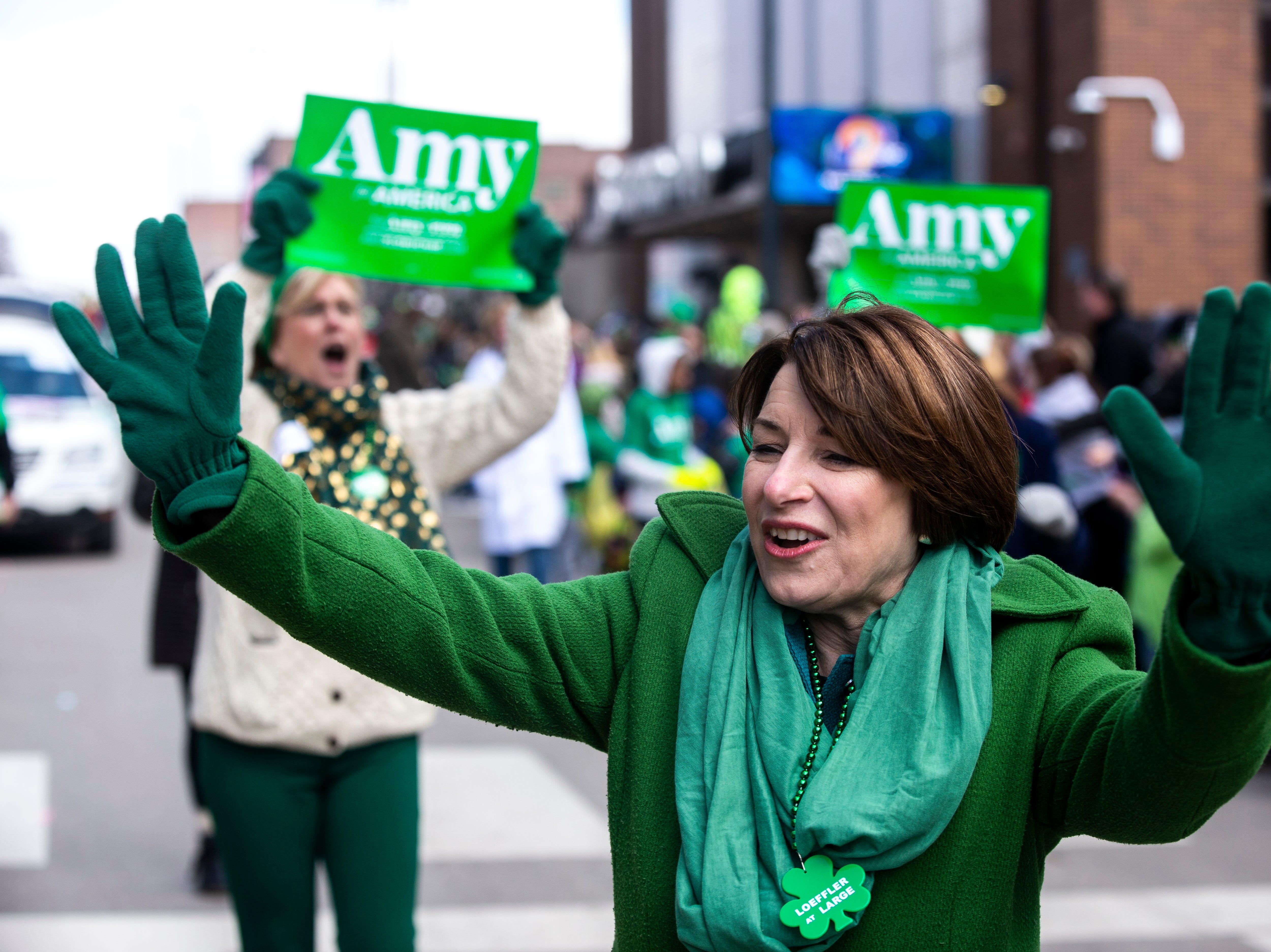 U.S. Sen. Amy Klobuchar, D-Minn., waves to people while walking in the Saint Patrick's Day Parade Society (SaPaDaPaSo) parade on Sunday, March 17, 2019, in downtown Cedar Rapids, Iowa.