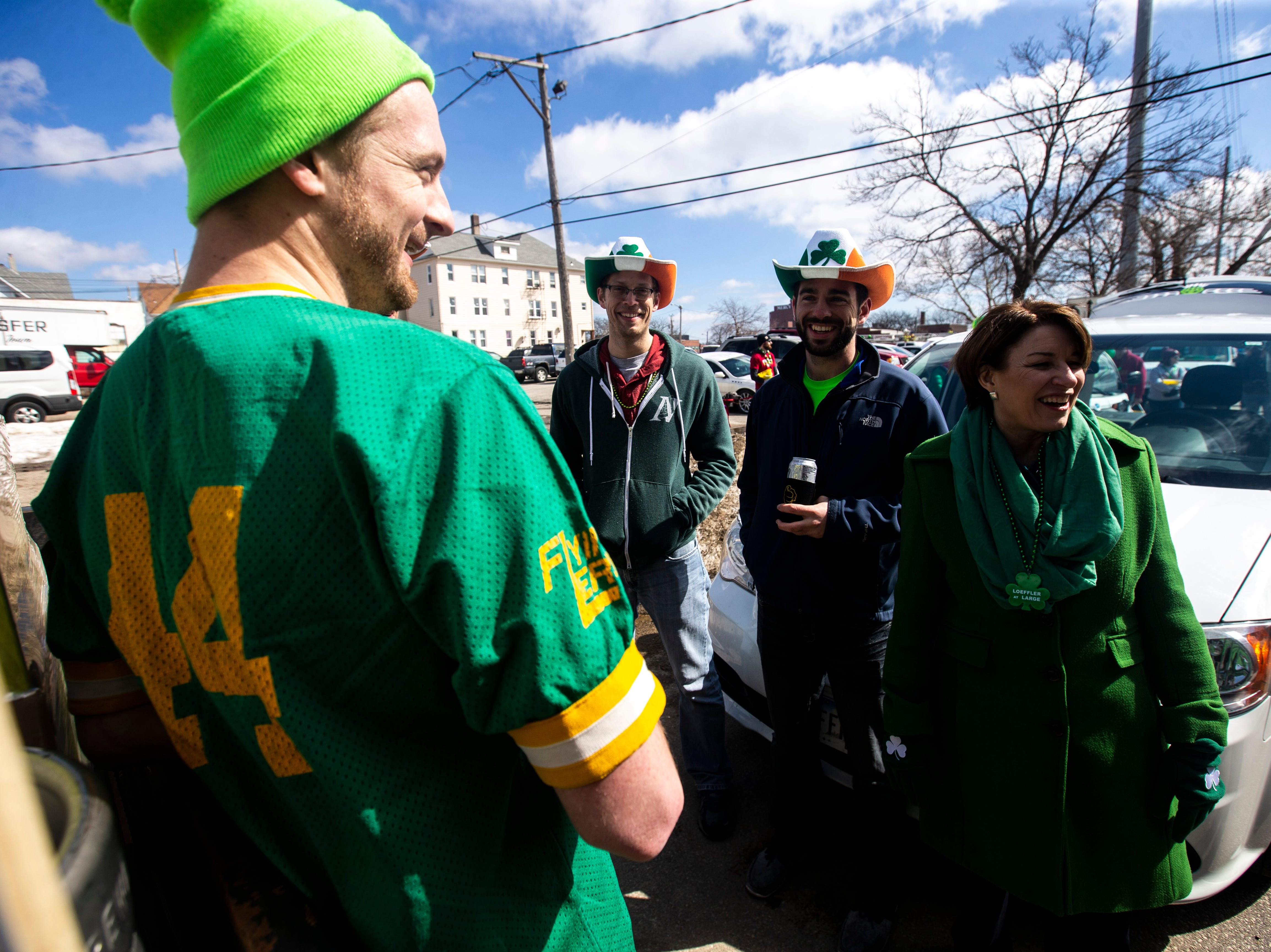 U.S. Sen. Amy Klobuchar, D-Minn., talks with employees from Iowa Brewing Co. in the staging area before walking in the Saint Patrick's Day Parade Society (SaPaDaPaSo) parade on Sunday, March 17, 2019, in downtown Cedar Rapids, Iowa.