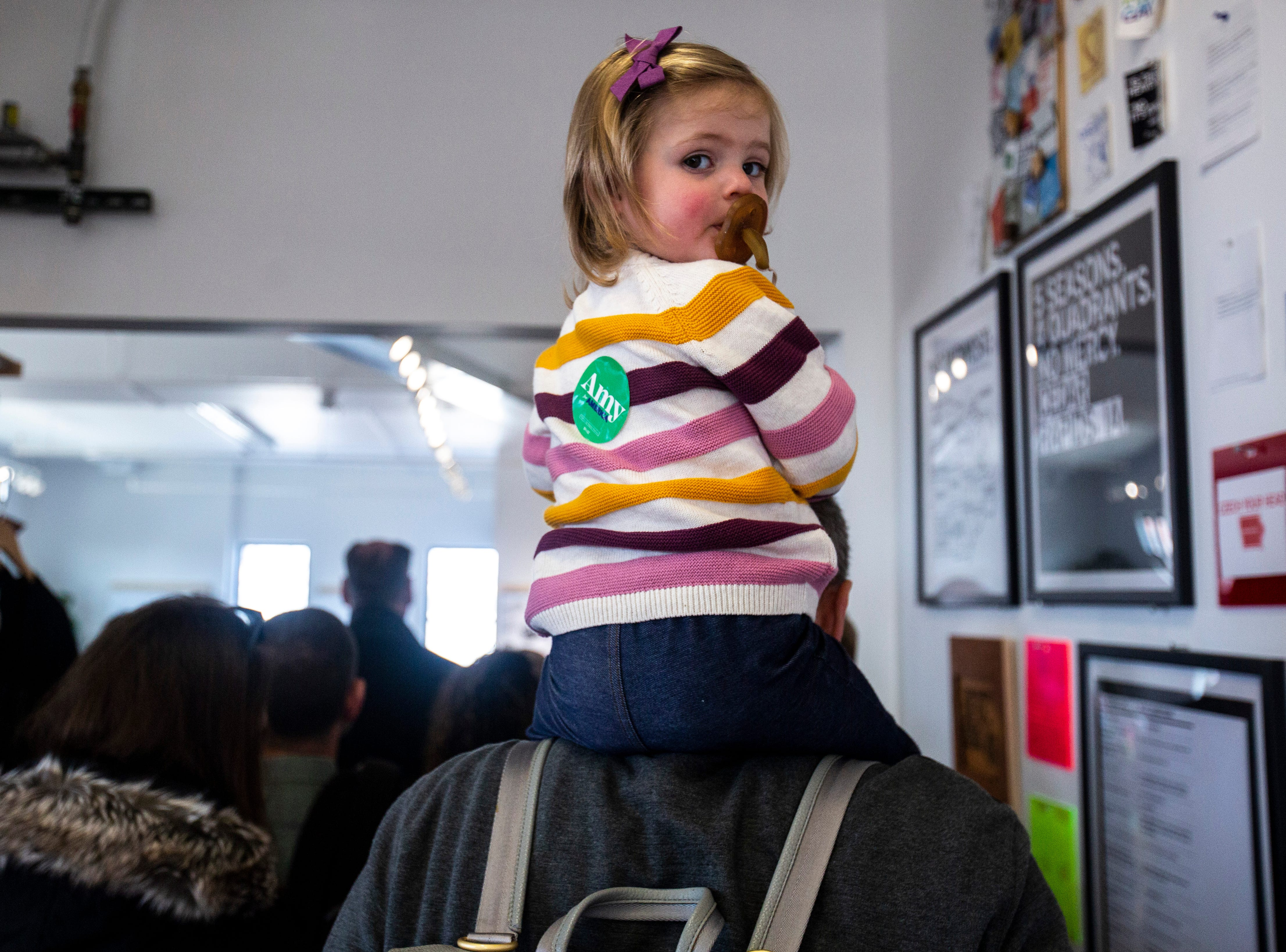 """Scout Crow, 1, looks over her shoulder while sitting on the shoulders of her father Tom Crow while U.S. Sen. Amy Klobuchar, D-Minn., speaks to the Linn County Phoenix Club on Sunday, March 17, 2019, at Raygun, a t-shirt store, in downtown Cedar Rapids, Iowa. Tom Crow and family recently moved from Minnesota, saying he came out to hear the senator speak because, """"None of this stuff happens there,"""" adding that he is excited to learn about the candidates while they come through Iowa."""