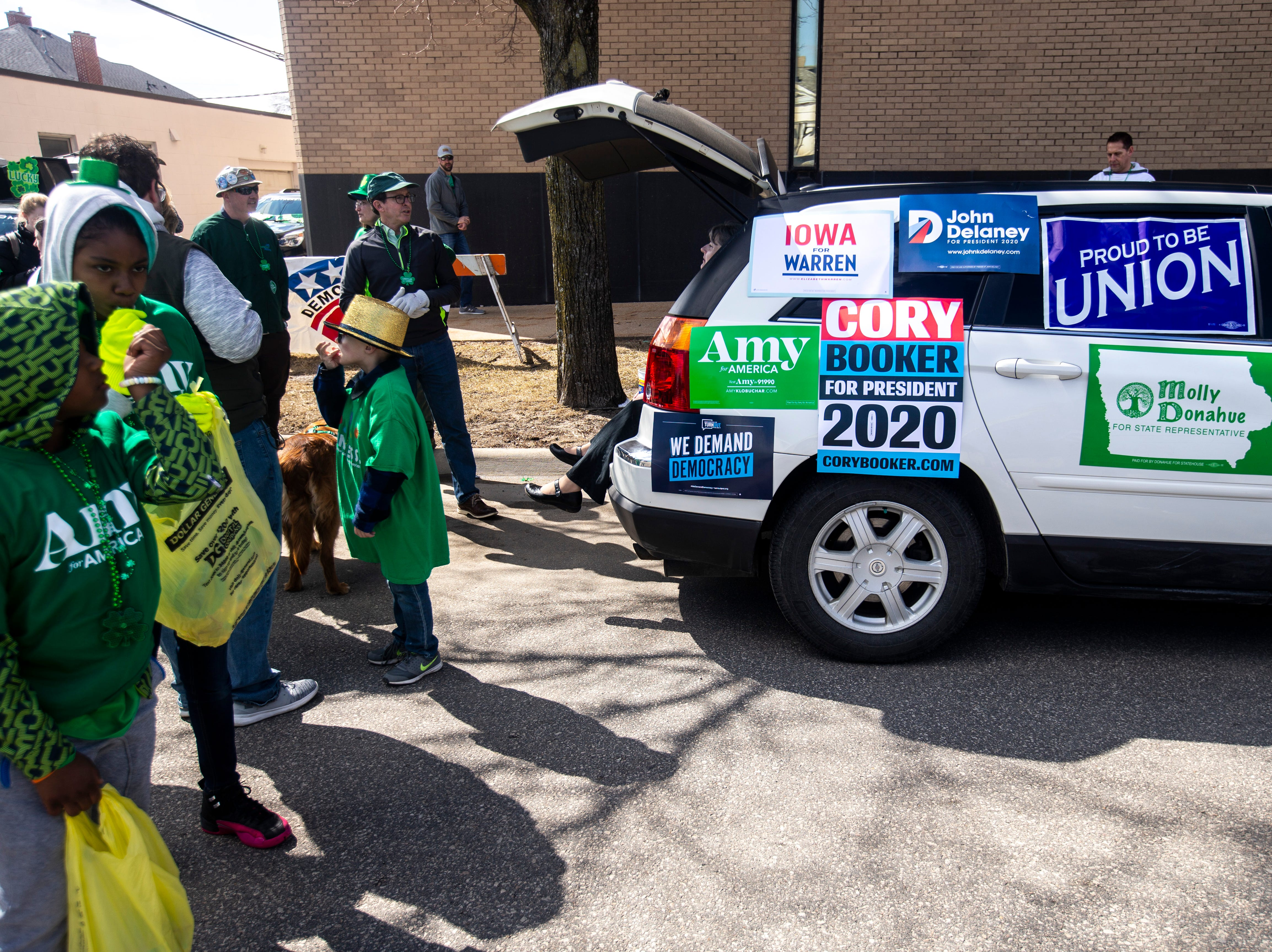 A vehicle in the Linn County Democrats float is covered in signs for Elizabeth Warren, Cory Booker, Amy Klobuchar, John Delaney, Bernie Sanders, and local candidates before the Saint Patrick's Day Parade Society (SaPaDaPaSo) parade on Sunday, March 17, 2019, in downtown Cedar Rapids, Iowa.