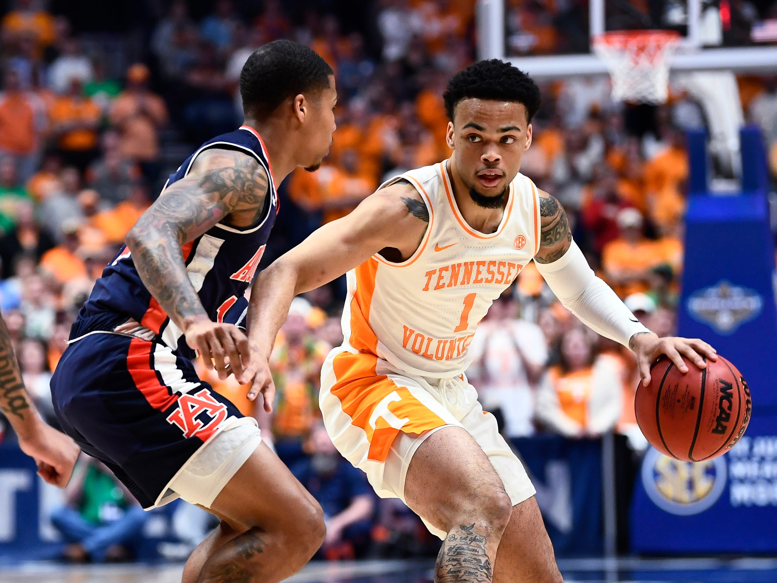 Tennessee guard Lamonte Turner (1) moves the ball defended by Auburn guard J'Von McCormick (12) during the first half of the SEC Men's Basketball Tournament championship game at Bridgestone Arena in Nashville, Tenn., Sunday, March 17, 2019.