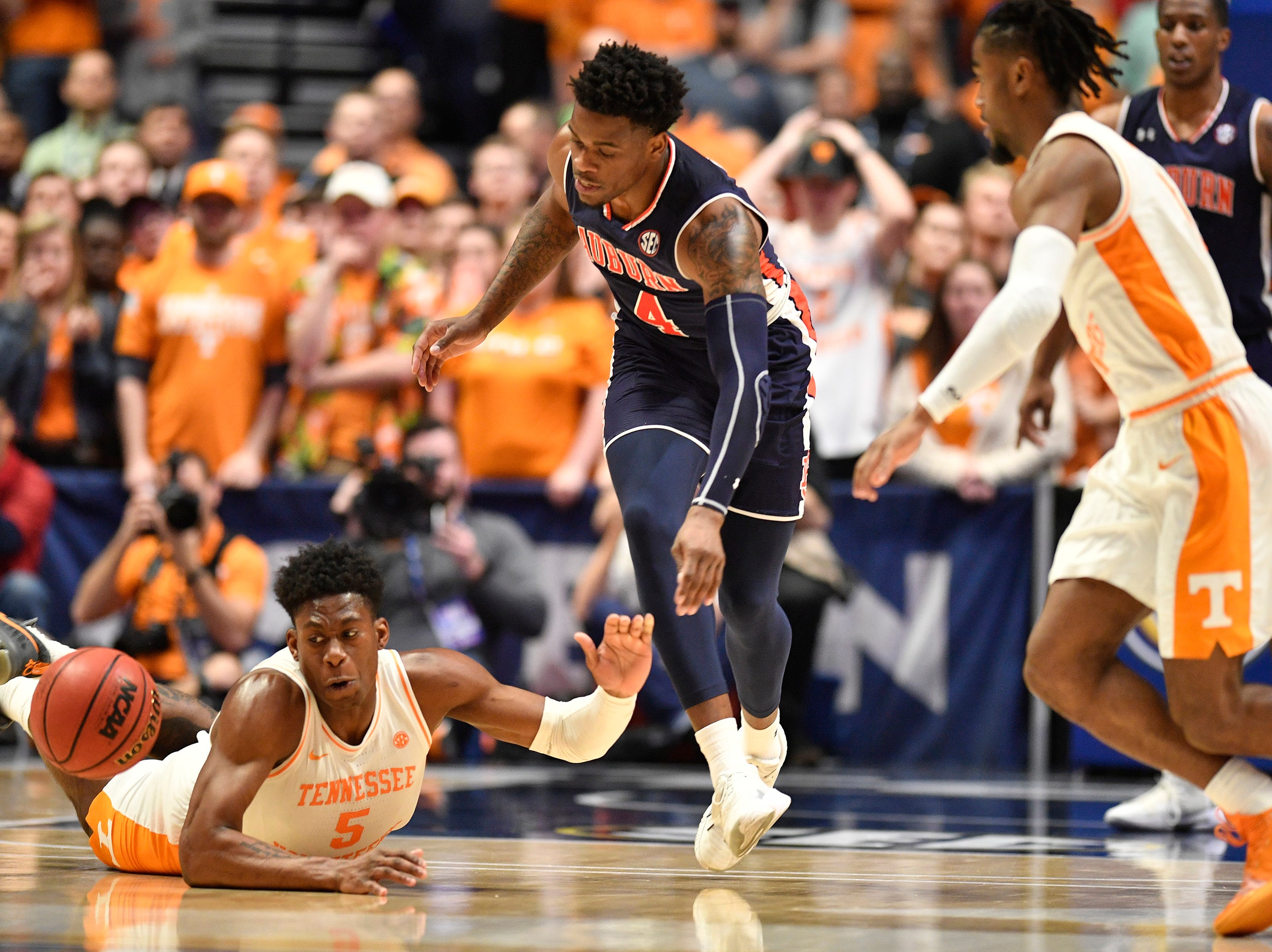 Tennessee guard Admiral Schofield (5), Auburn guard/forward Malik Dunbar (4) and Tennessee guard Jordan Bone (0) battle for a loose ball during the second half of the SEC Men's Basketball Tournament championship game at Bridgestone Arena in Nashville, Tenn., Sunday, March 17, 2019.