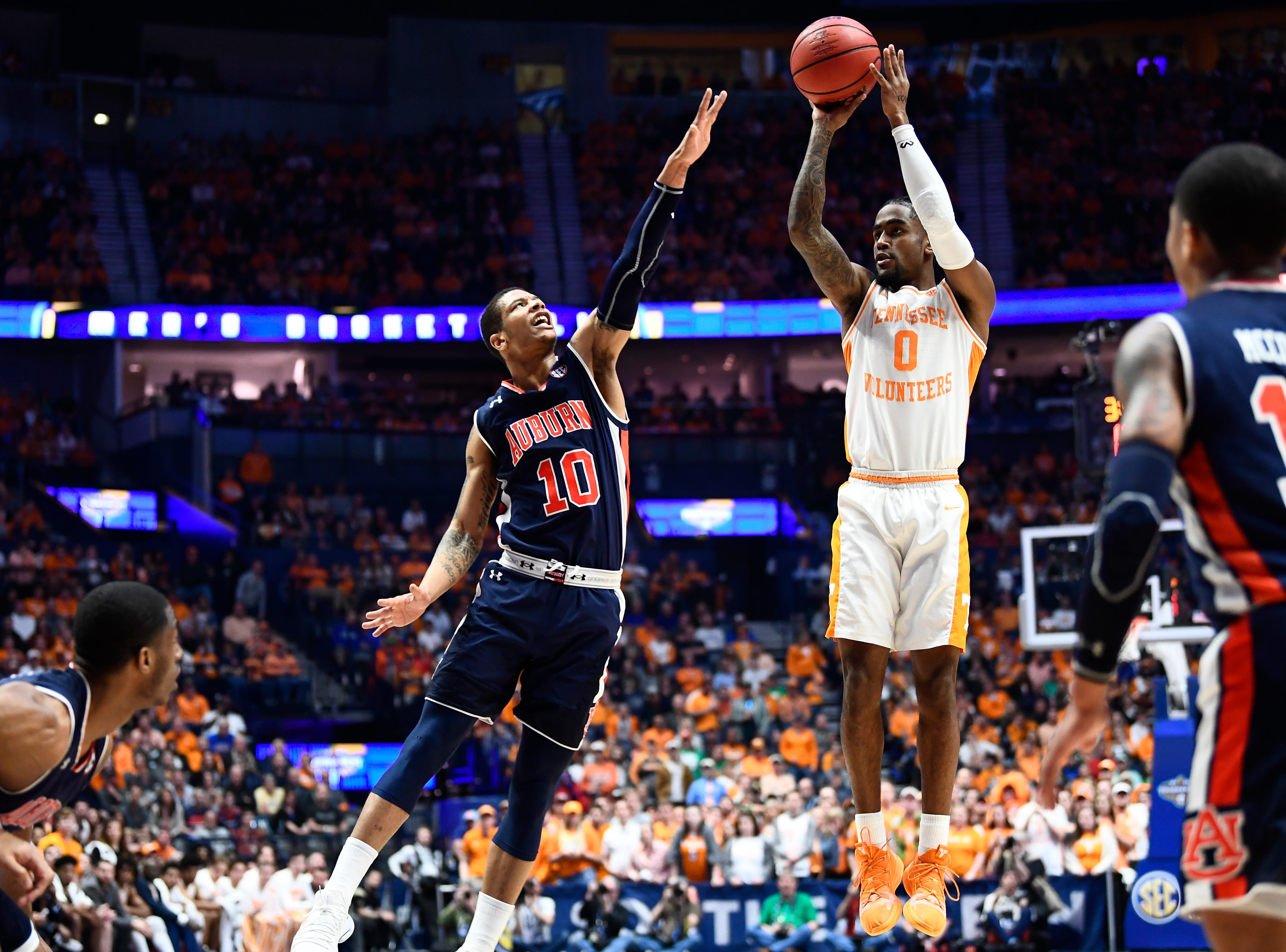 Tennessee guard Jordan Bone (0) takes a shot while defended by by Auburn guard Samir Doughty (10) during the first half of the SEC Men's Basketball Tournament championship game at Bridgestone Arena in Nashville, Tenn., Sunday, March 17, 2019.