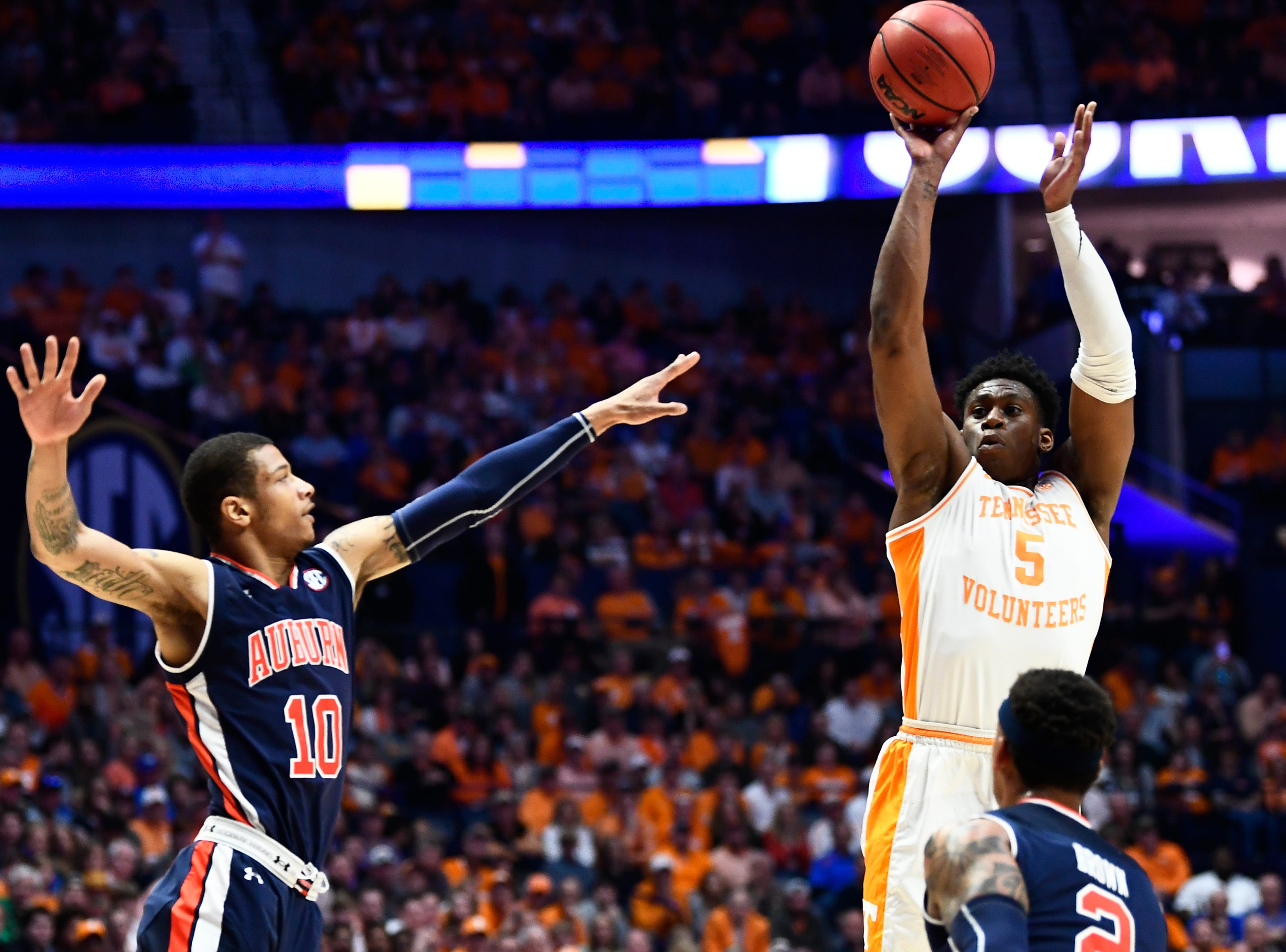 Tennessee guard Admiral Schofield (5) takes a shot while defended by Auburn guard Samir Doughty (10) and Auburn guard Bryce Brown (2) during the first half of the SEC Men's Basketball Tournament championship game at Bridgestone Arena in Nashville, Tenn., Sunday, March 17, 2019.