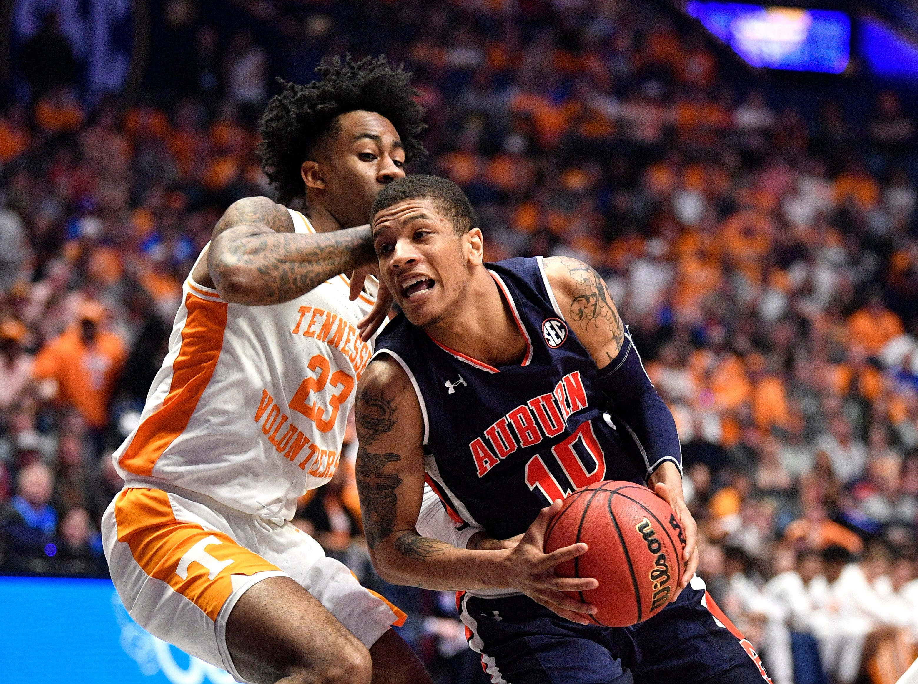 Auburn guard Samir Doughty (10) moves the ball defended by Tennessee guard Jordan Bowden (23) during the second half of the SEC Men's Basketball Tournament championship game at Bridgestone Arena in Nashville, Tenn., Sunday, March 17, 2019.