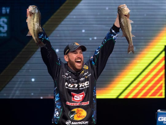 Knoxville's Ott DeFoe shows off his two best bass of day's catch to win the 2019 Bassmaster Classic on Sunday, March 17, 2019 during the weigh-in at Thompson-Boling Arena. DeFoe won with a total of 49 lbs and 3 oz. of bass fish over the three day tournament.