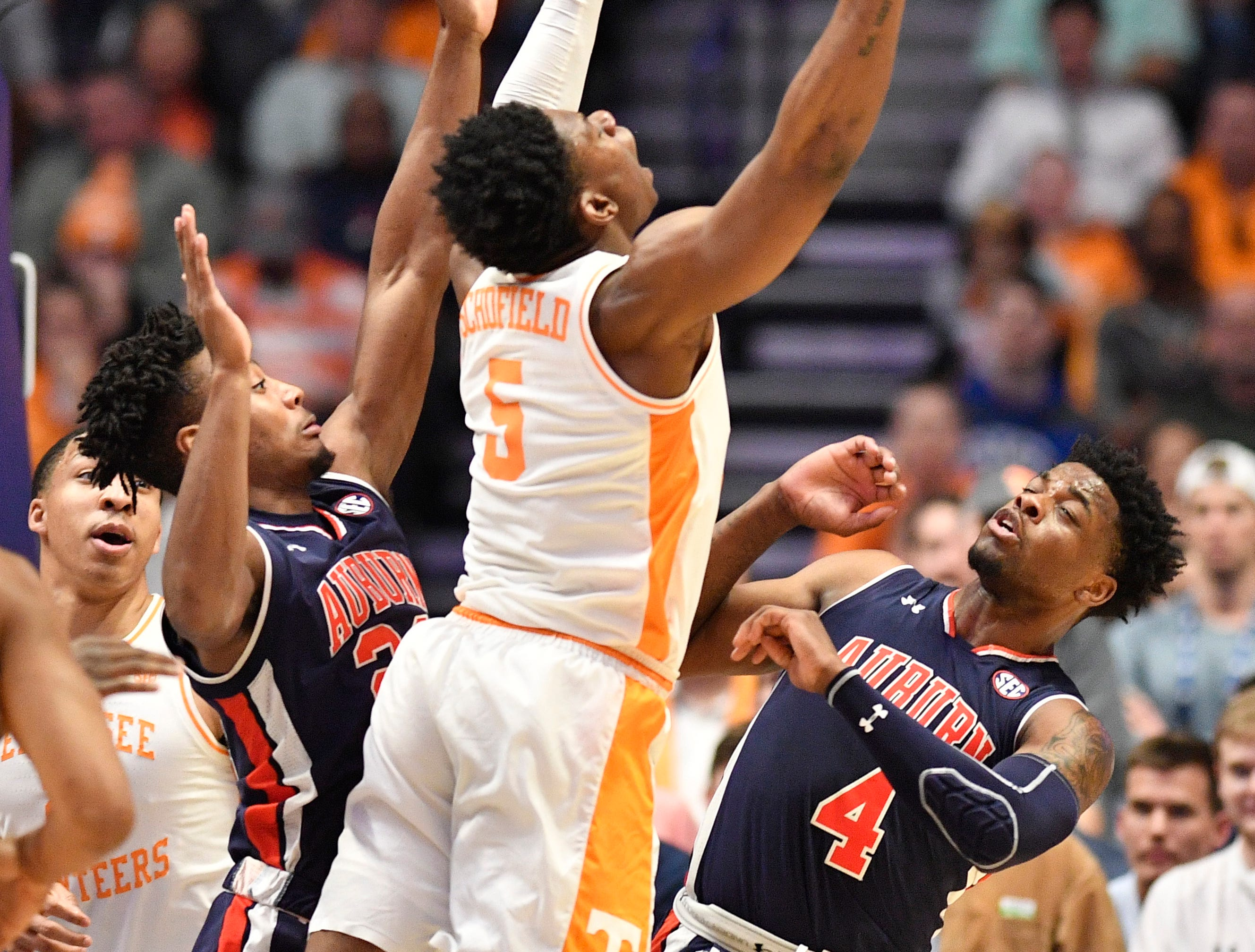 Auburn forward Anfernee McLemore (24), Tennessee guard Admiral Schofield (5) and Auburn guard/forward Malik Dunbar (4) battle for a loose ball during the first half of the SEC Men's Basketball Tournament championship game at Bridgestone Arena in Nashville, Tenn., Sunday, March 17, 2019.