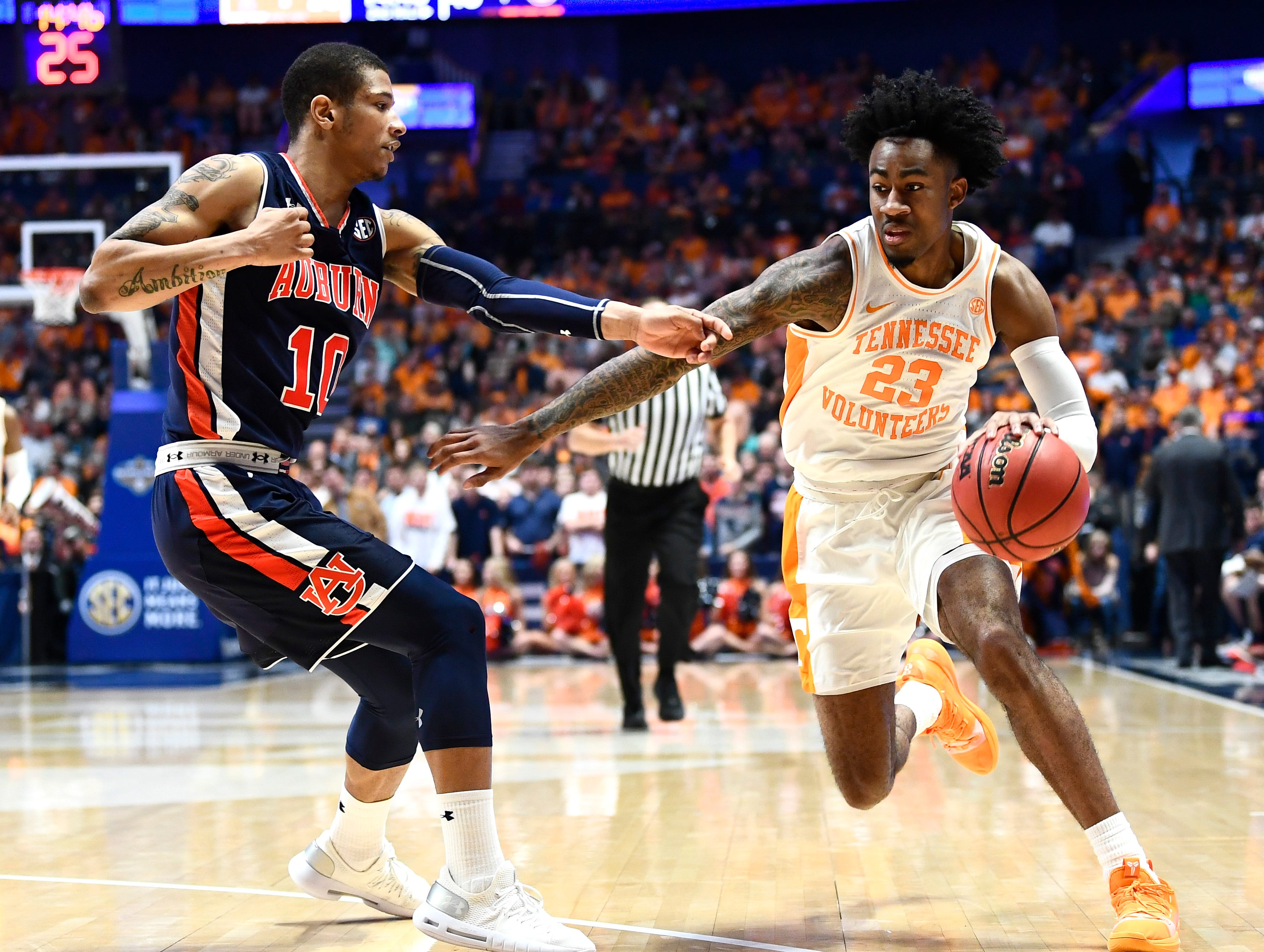 Tennessee guard Jordan Bowden (23) moves the ball defended by Auburn guard Samir Doughty (10)during the second half of the SEC Men's Basketball Tournament championship game at Bridgestone Arena in Nashville, Tenn., Sunday, March 17, 2019.