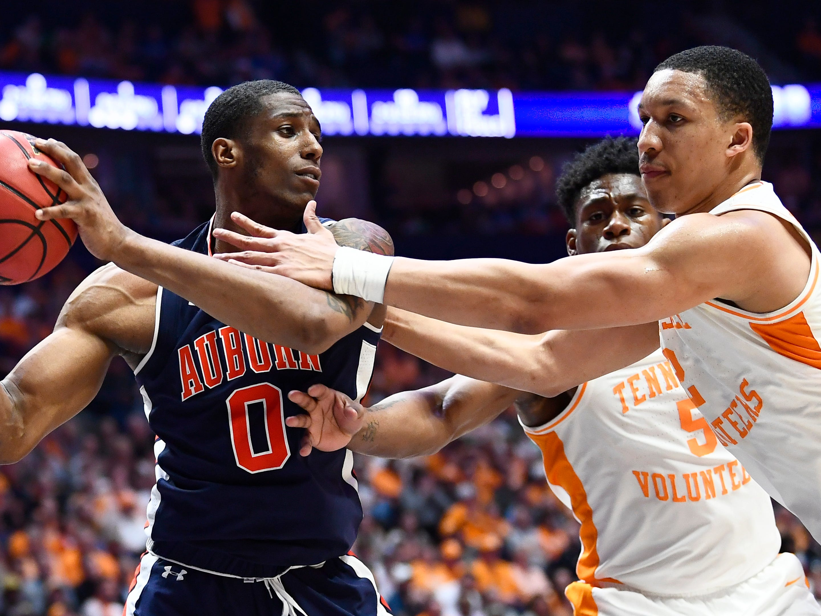 Auburn forward Horace Spencer (0) moves the ball defended by Tennessee guard Admiral Schofield (5) and forward Grant Williams (2) during the second half of the SEC Men's Basketball Tournament championship game at Bridgestone Arena in Nashville, Tenn., Sunday, March 17, 2019.