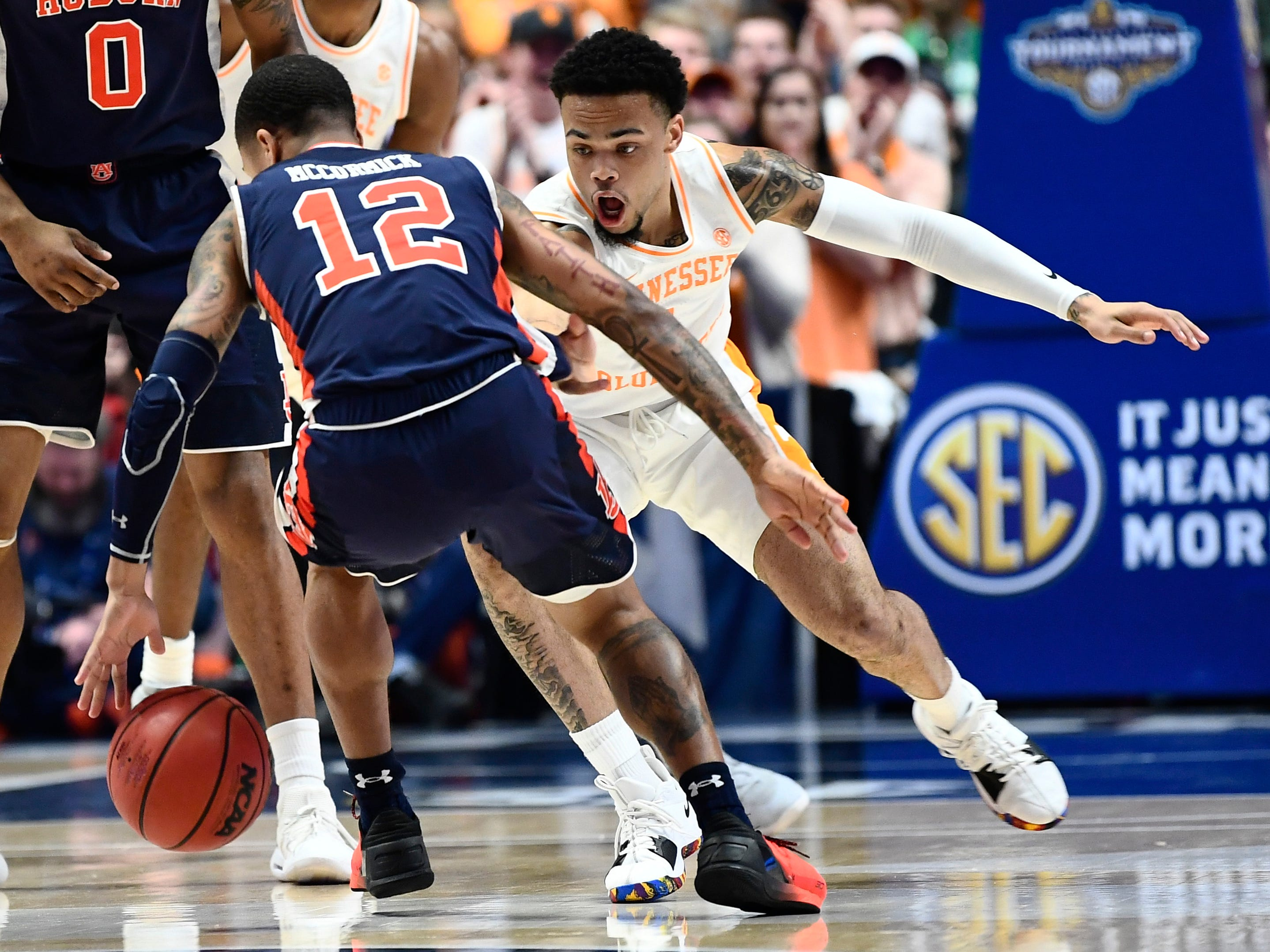 Auburn guard J'Von McCormick (12) moves the ball defended by Tennessee guard Lamonte Turner (1) during the first half of the SEC Men's Basketball Tournament championship game at Bridgestone Arena in Nashville, Tenn., Sunday, March 17, 2019.