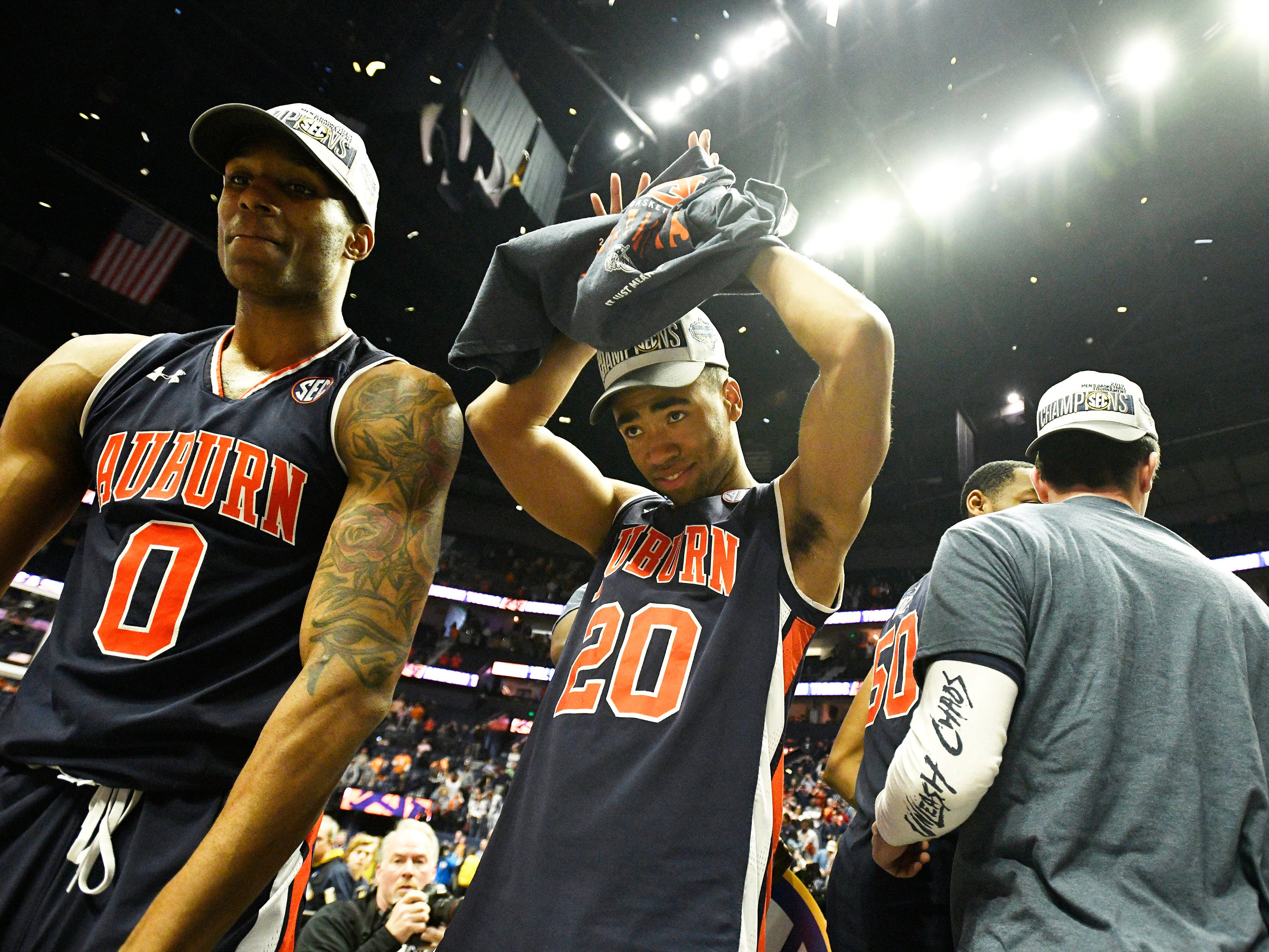 Auburn forward Myles Parker (20) puts on his championship t-shirt after the team defeated Tennessee in the SEC Men's Basketball Tournament championship game at Bridgestone Arena in Nashville, Tenn., Sunday, March 17, 2019.