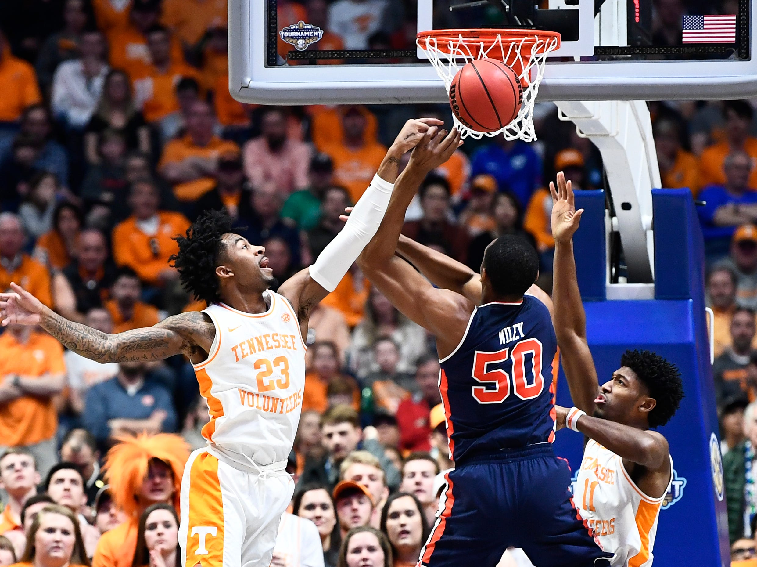 Tennessee guard Jordan Bowden (23) and Tennessee forward Kyle Alexander (11) defend Auburn center Austin Wiley (50) during the first half of the SEC Men's Basketball Tournament championship game at Bridgestone Arena in Nashville, Tenn., Sunday, March 17, 2019.