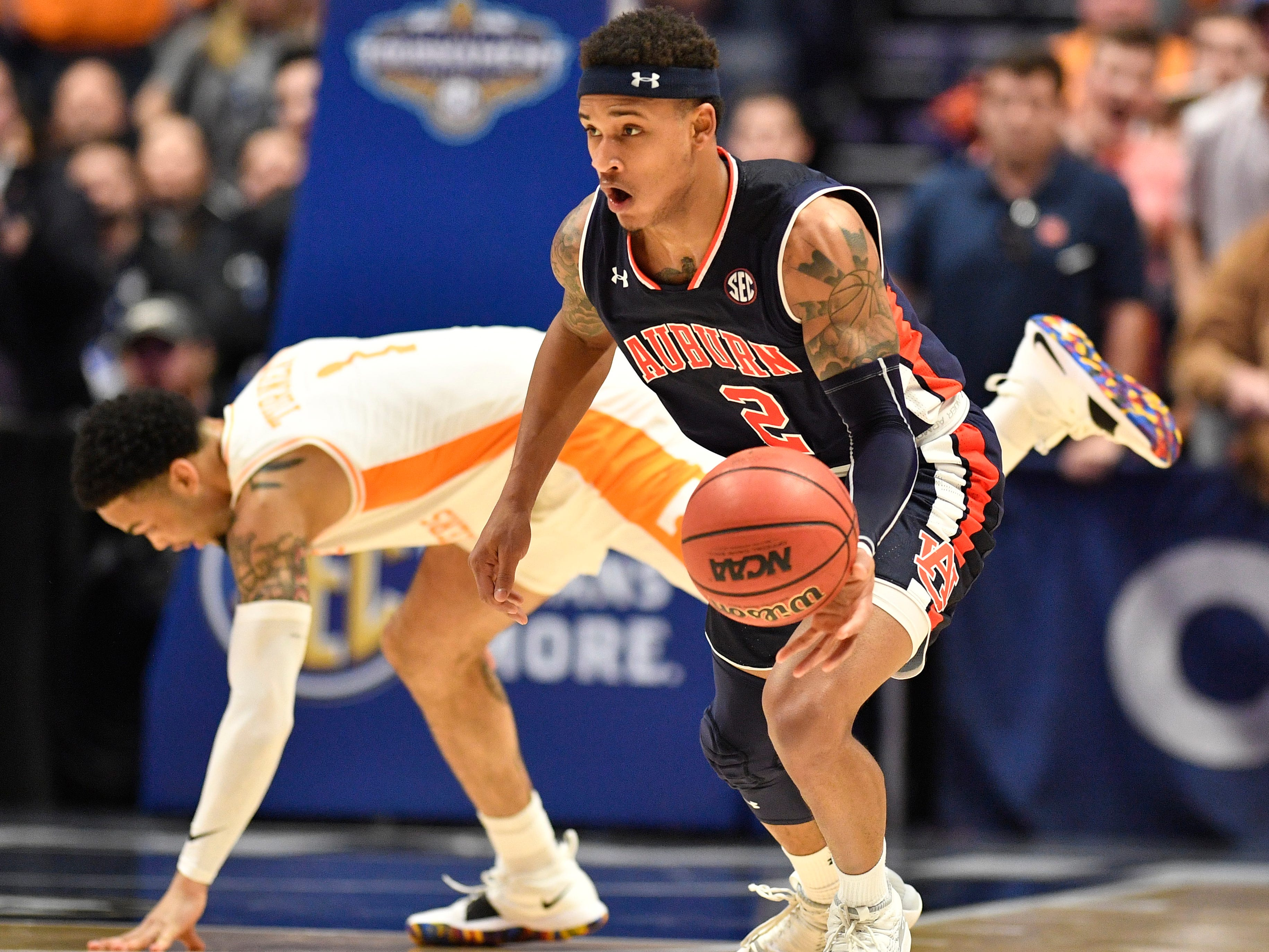 Auburn guard Bryce Brown (2) moves the ball as Tennessee guard Lamonte Turner (1) tumbles behind him during the first half of the SEC Men's Basketball Tournament championship game at Bridgestone Arena in Nashville, Tenn., Sunday, March 17, 2019.