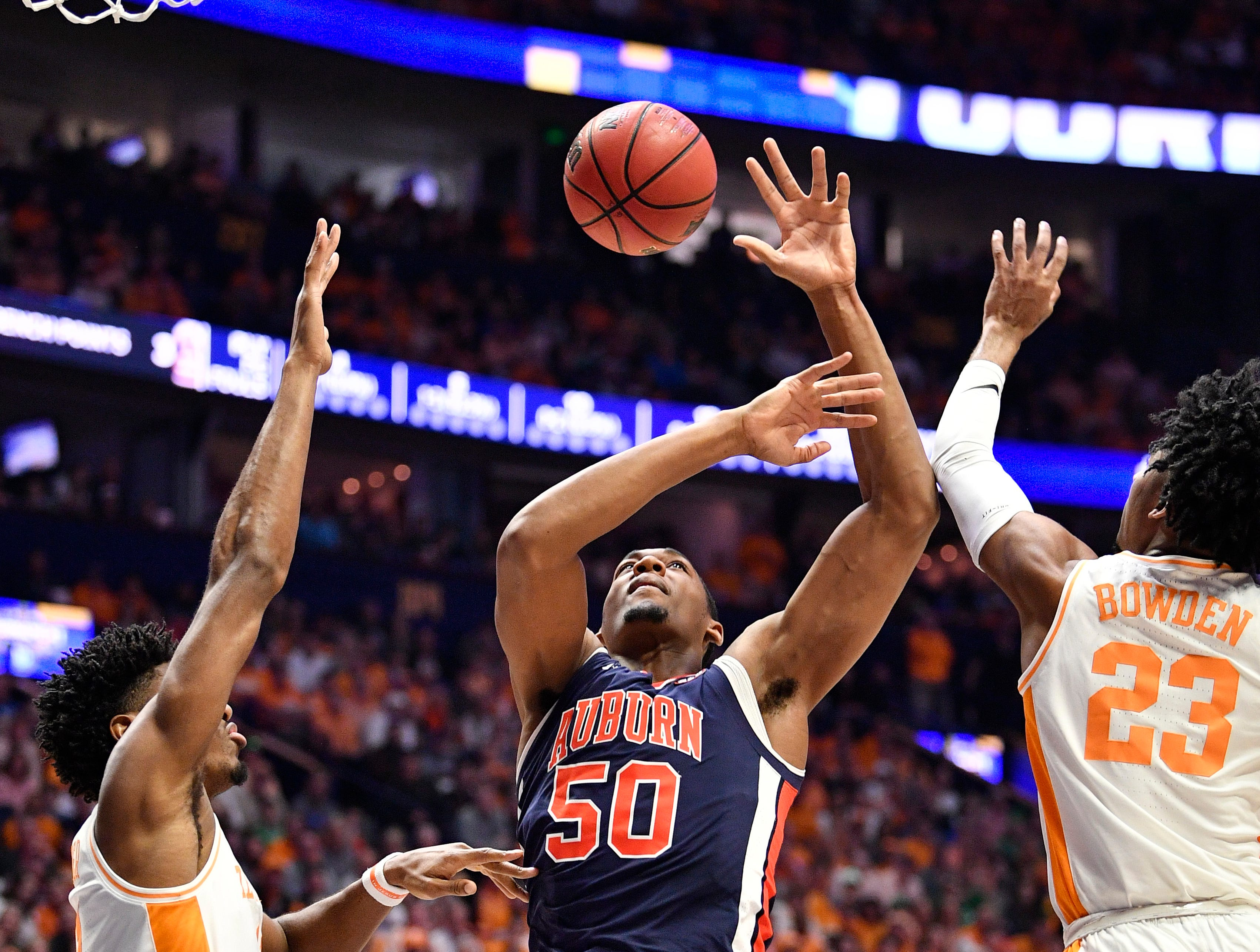 Auburn center Austin Wiley (50) loses the ball defended by Tennessee forward Kyle Alexander (11) and guard Jordan Bowden (23) during the first half of the SEC Men's Basketball Tournament championship game at Bridgestone Arena in Nashville, Tenn., Sunday, March 17, 2019.