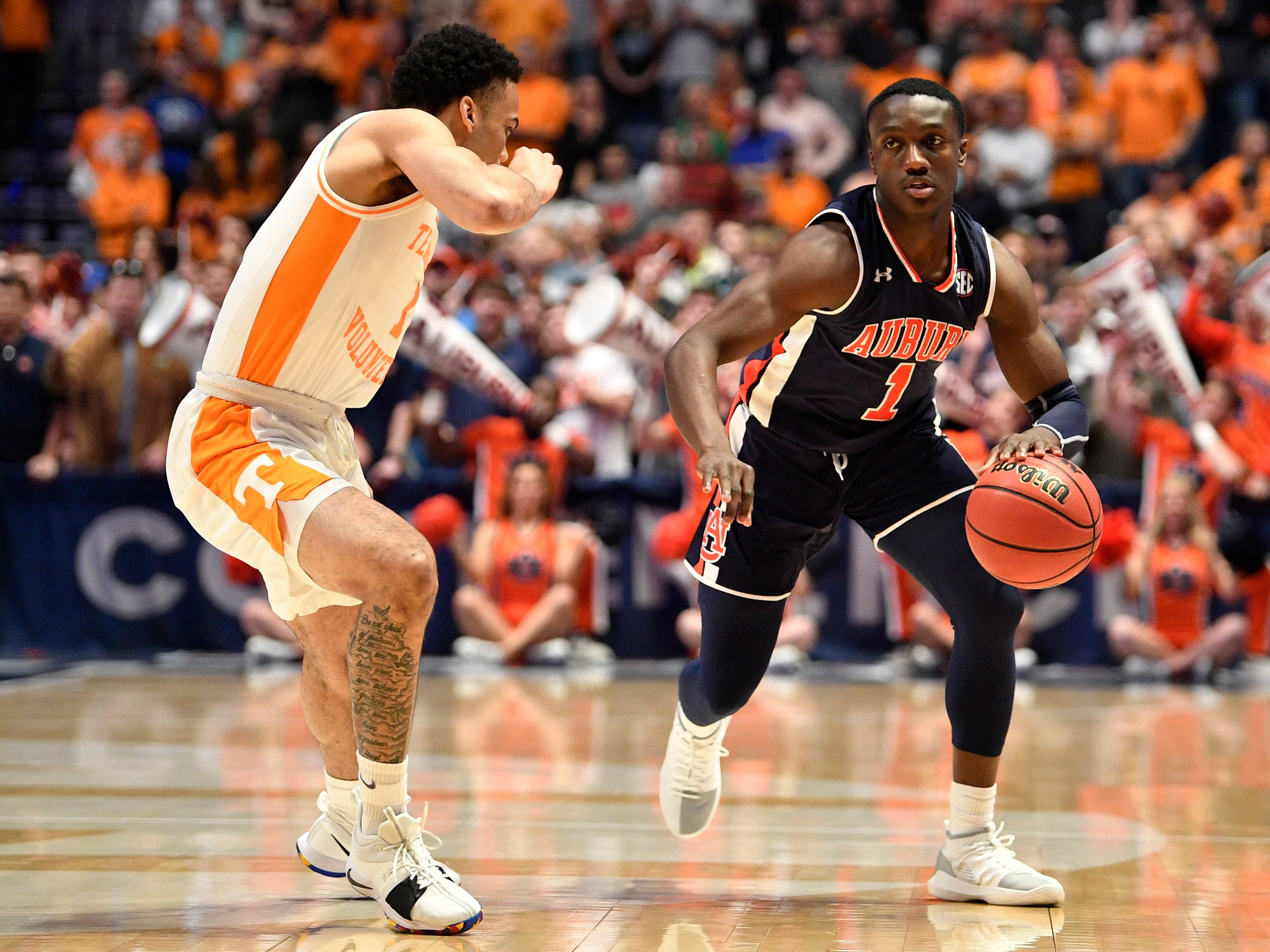 Auburn guard Jared Harper (1) moves the ball defended by Tennessee guard Lamonte Turner (1) during the first half of the SEC Men's Basketball Tournament championship game at Bridgestone Arena in Nashville, Tenn., Sunday, March 17, 2019.