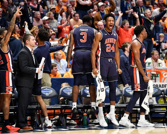 Auburn players Danjel Purifoy (3), Anfernee McLemore (24) and Malik Dunbar (4) cheer on the bench during the second half of the SEC Tournament championship game against Tennessee at Bridgestone Arena in Nashville, Tenn., Sunday, March 17, 2019.