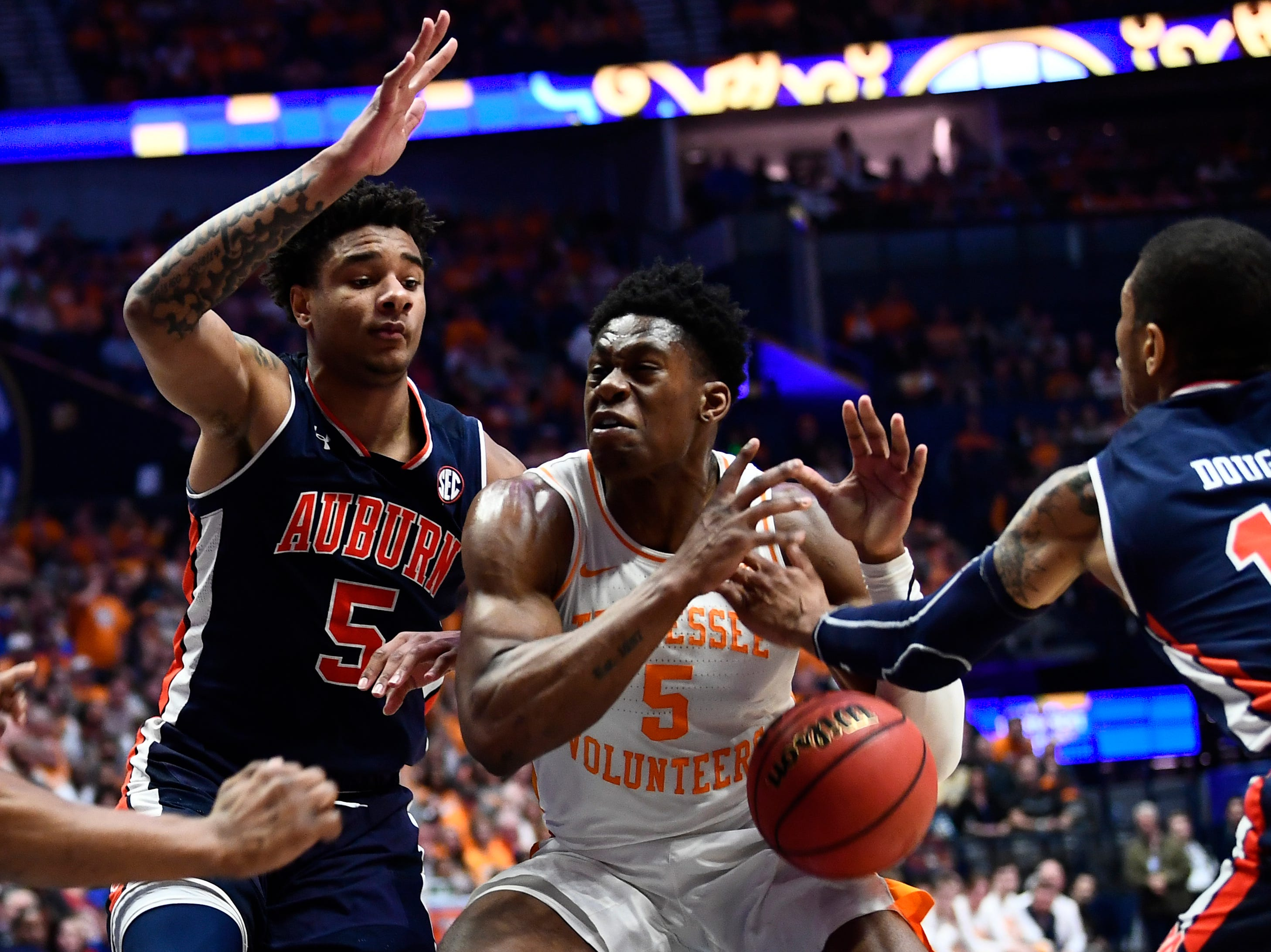 Tennessee guard Admiral Schofield (5) gets the ball knocked out of his possession by Auburn guard Samir Doughty (10) during the first half of the SEC Men's Basketball Tournament championship game at Bridgestone Arena in Nashville, Tenn., Sunday, March 17, 2019.