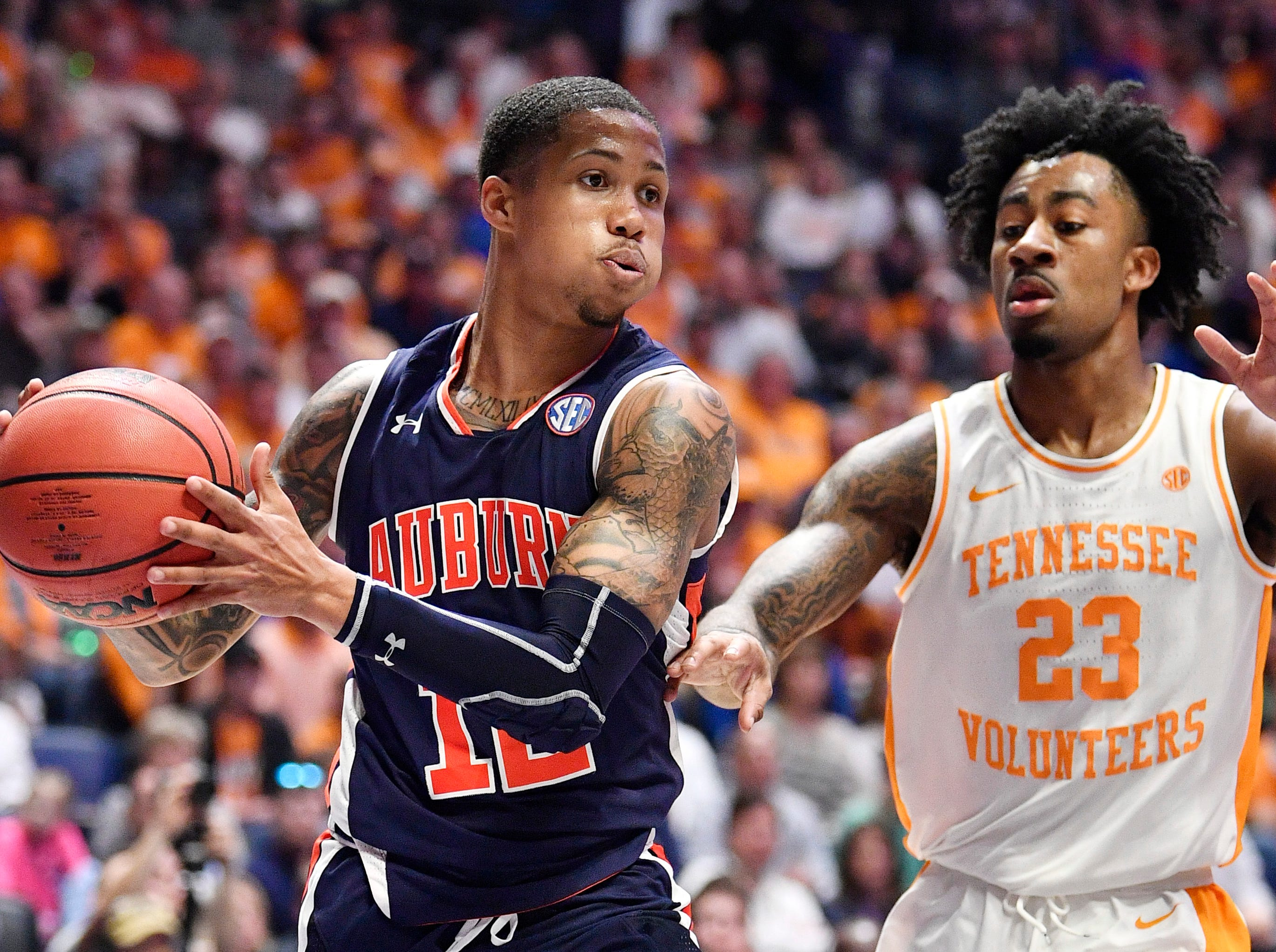 Auburn guard J'Von McCormick (12) moves the ball defended by Tennessee guard Jordan Bowden (23) during the first half of the SEC Men's Basketball Tournament championship game at Bridgestone Arena in Nashville, Tenn., Sunday, March 17, 2019.
