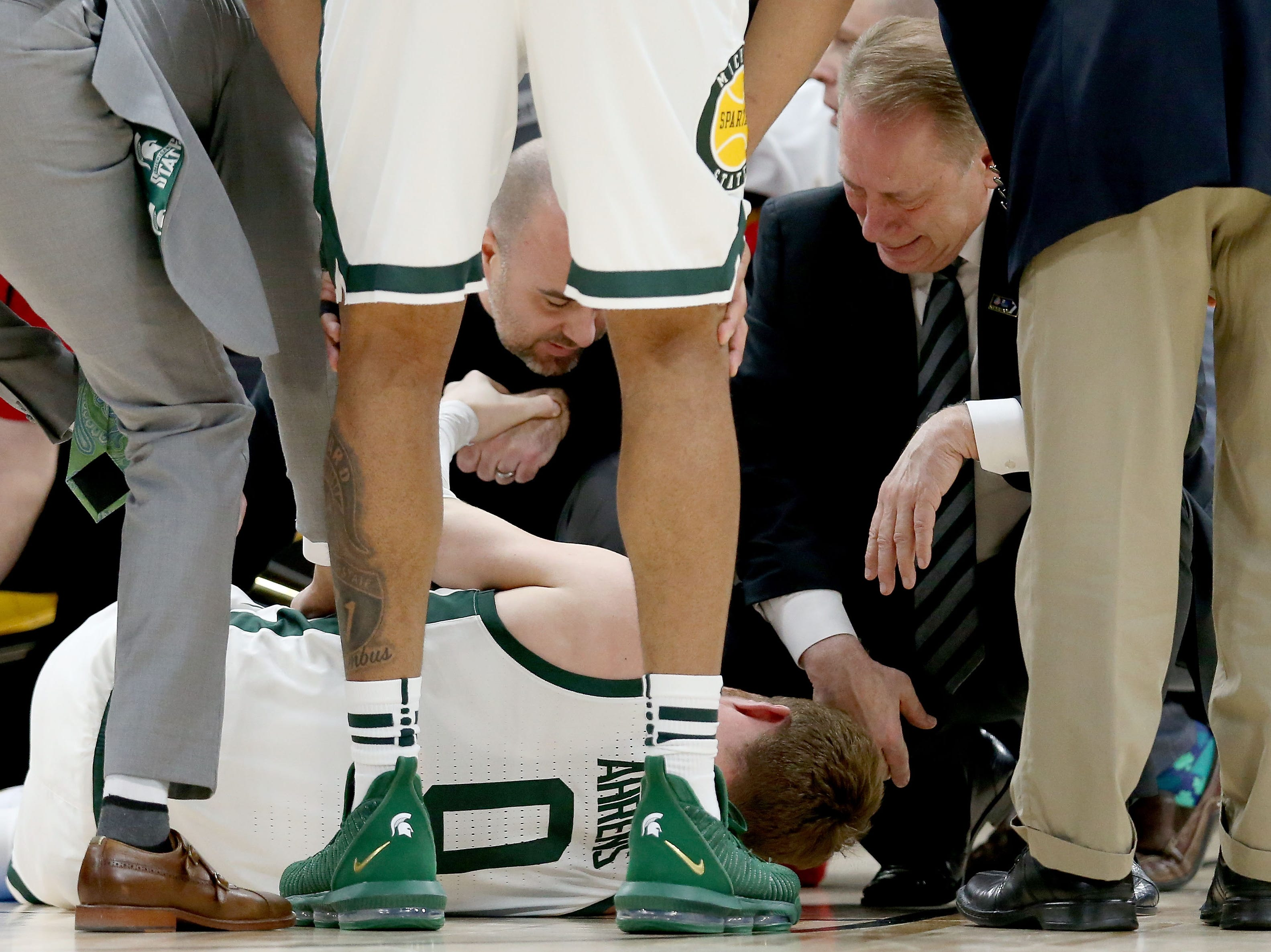 Head coach Tom Izzo of the Michigan State Spartans attends to Kyle Ahrens #0 after being injured in the first half against the Michigan Wolverines during the championship game of the Big Ten Basketball Tournament at the United Center on March 17, 2019 in Chicago, Illinois.