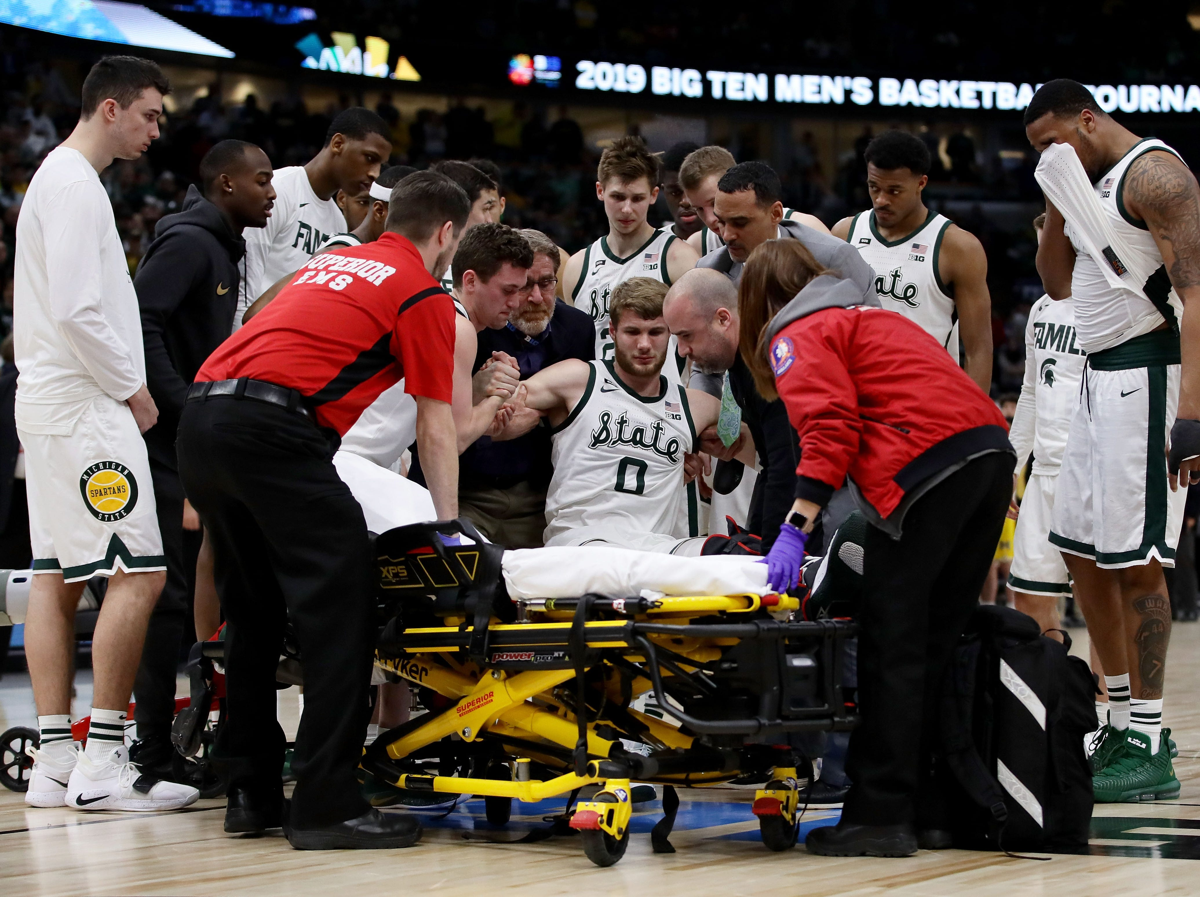 Kyle Ahrens #0 of the Michigan State Spartans is attended to after being injured in the first half against the Michigan Wolverines during the championship game of the Big Ten Basketball Tournament at the United Center on March 17, 2019 in Chicago, Illinois.