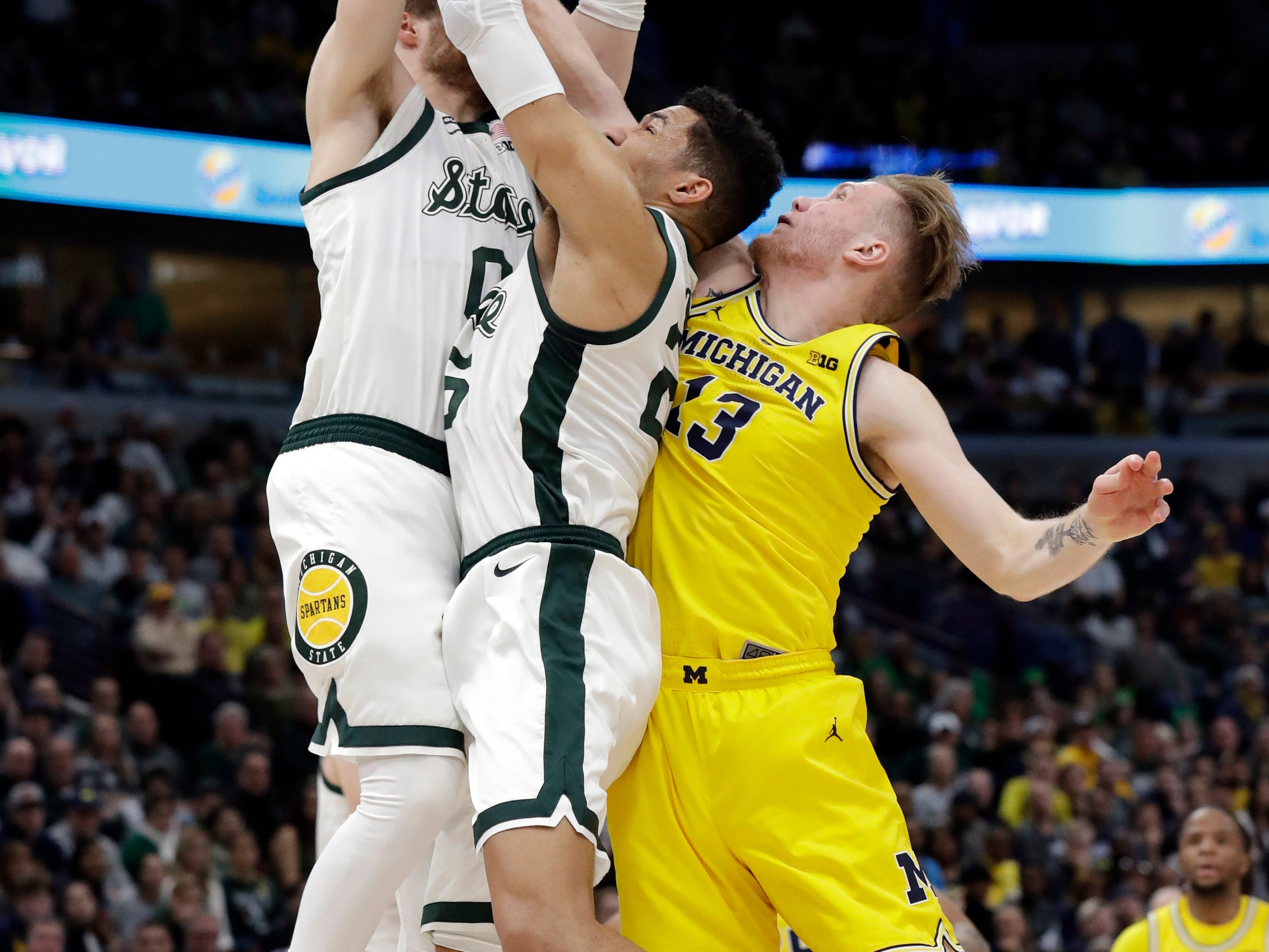 Michigan State's Kyle Ahrens (0), Kenny Goins (25) and Michigan's Ignas Brazdeikis (13) battle for a rebound during the first half of an NCAA college basketball championship game in the Big Ten Conference tournament, Sunday, March 17, 2019, in Chicago. Ahrens was injured on this play and taken off the court.