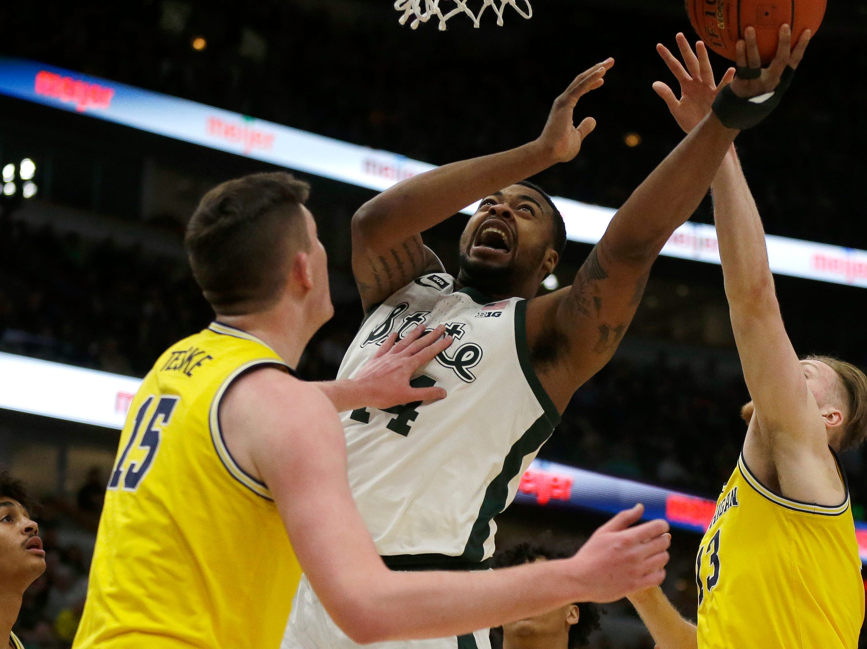 Michigan State's Nick Ward (44) goes up for a shot against Michigan's Jon Teske (15) and Ignas Brazdeikis (13) during the first half of an NCAA college basketball championship game in the Big Ten Conference tournament, Sunday, March 17, 2019, in Chicago.