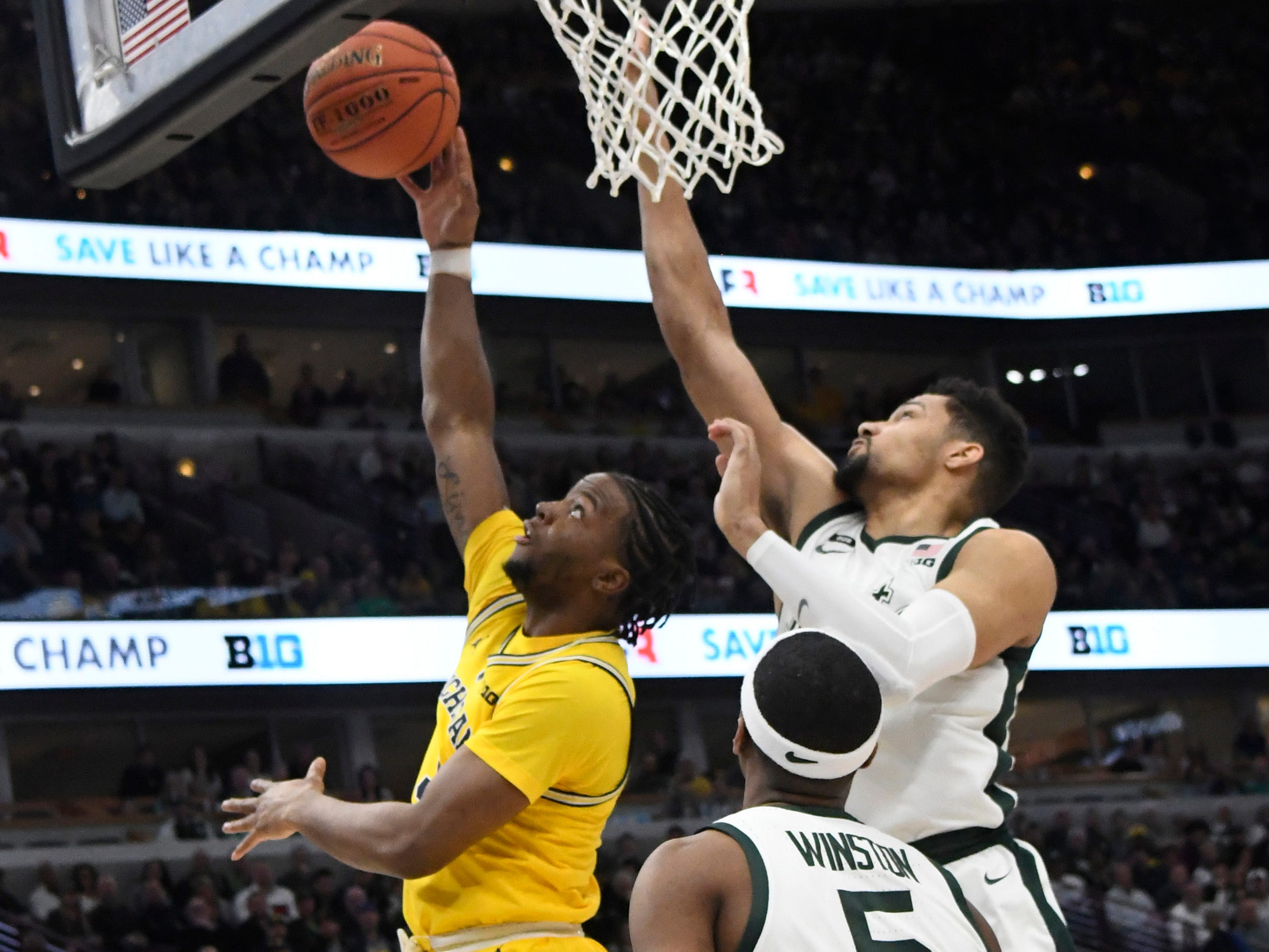 Michigan Wolverines guard Adrien Nunez (5) is defended by Michigan State Spartans forward Kenny Goins (25) during the first half in the Big Ten conference tournament at United Center.