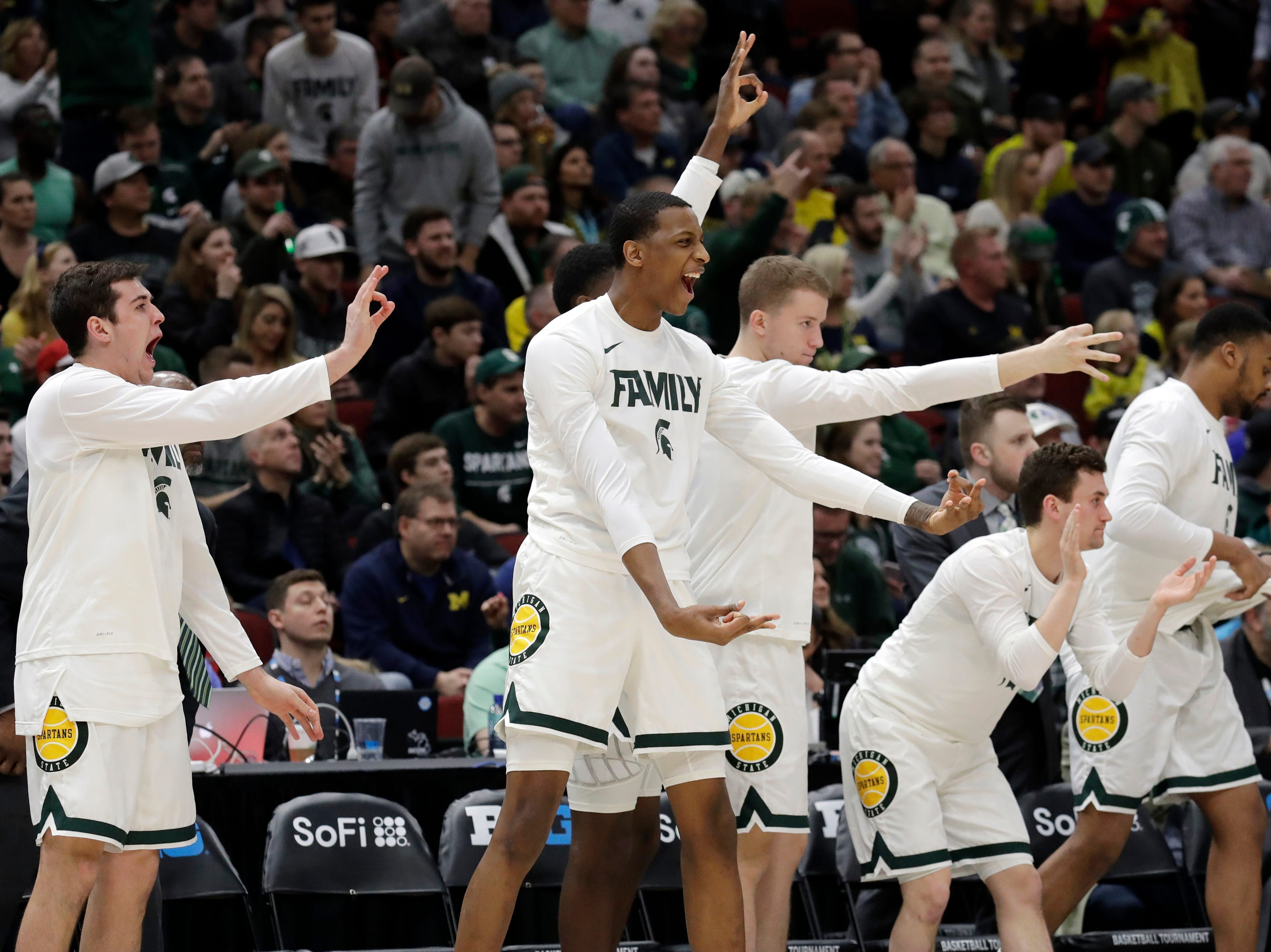 Michigan State bench celebrate after Matt McQuaid shoots a 3-point basket during the first half of an NCAA college basketball championship game against Michigan in the Big Ten Conference tournament, Sunday, March 17, 2019, in Chicago.